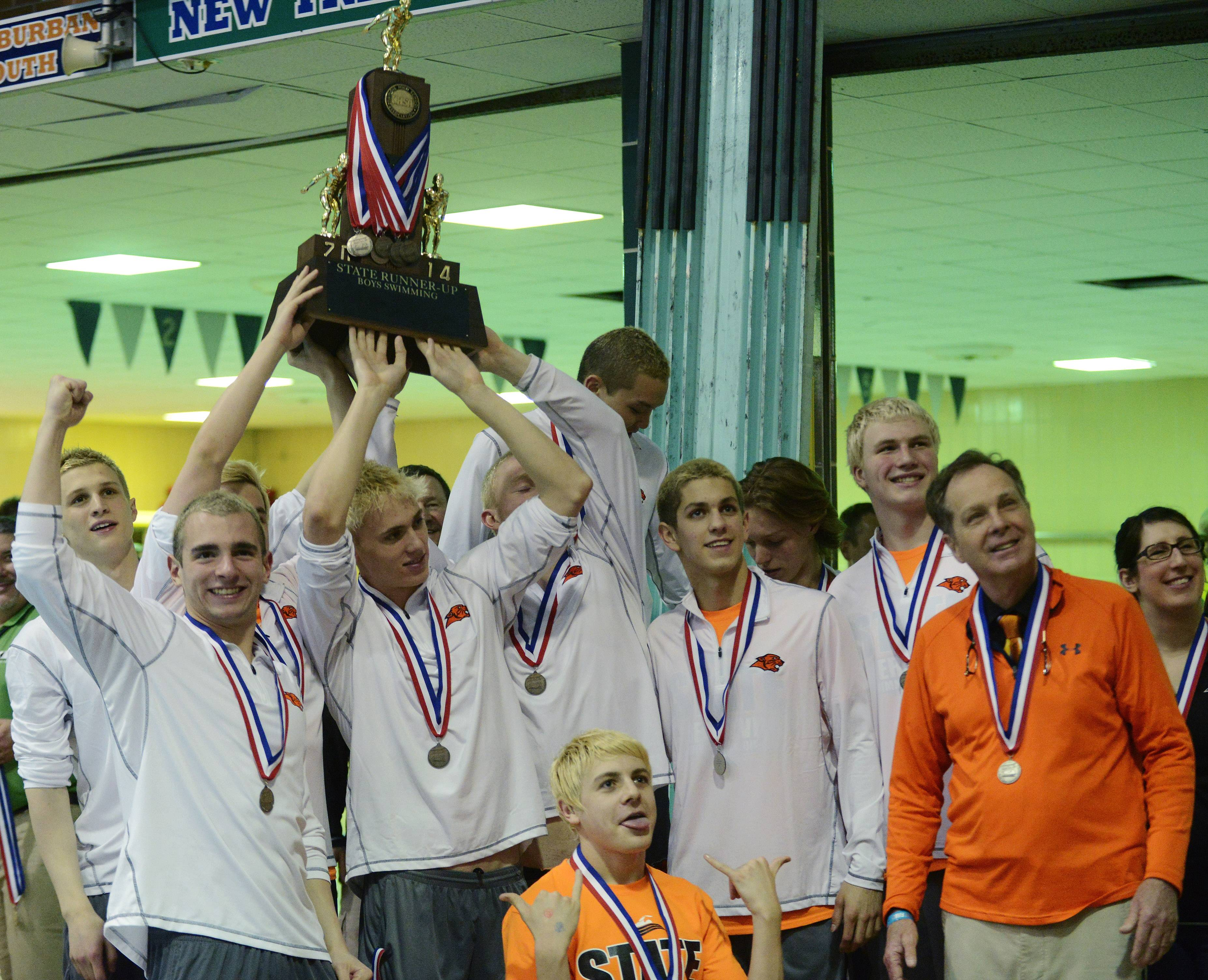 Libertyville swimmers hoist their second-place team trophy following the boys swimming state meet finals at Evanston High School on Saturday.