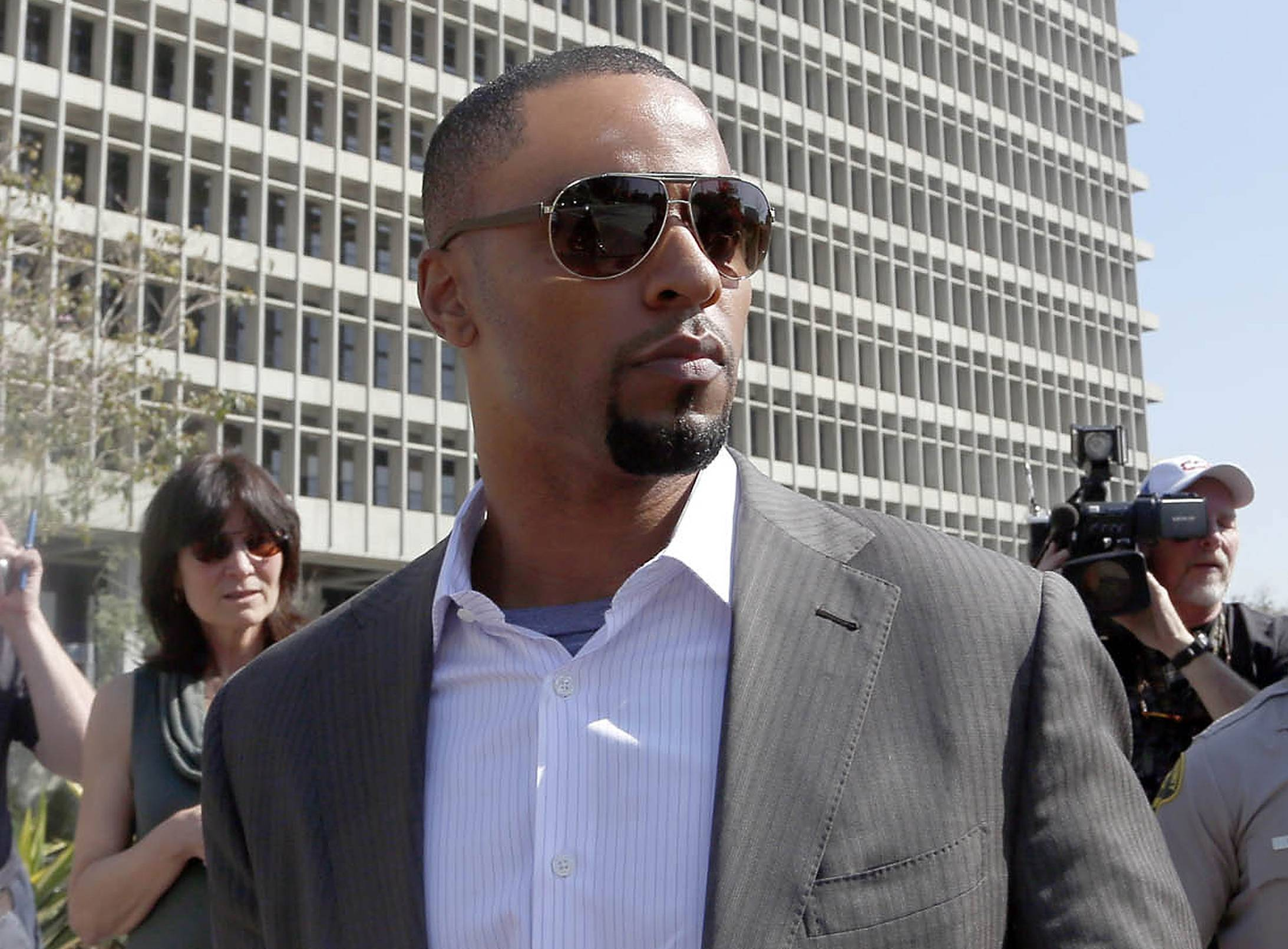 In this Feb. 14, 2014, photo, former NFL safety Darren Sharper leaves a courthouse in Los Angeles. An arrest warrant has been issued for Sharper and another man, accusing them of raping two women in New Orleans last year. Sharper also is under investigation in sexual assault cases in Florida, Nevada and Arizona and has pleaded not guilty to rape charges in Los Angeles.