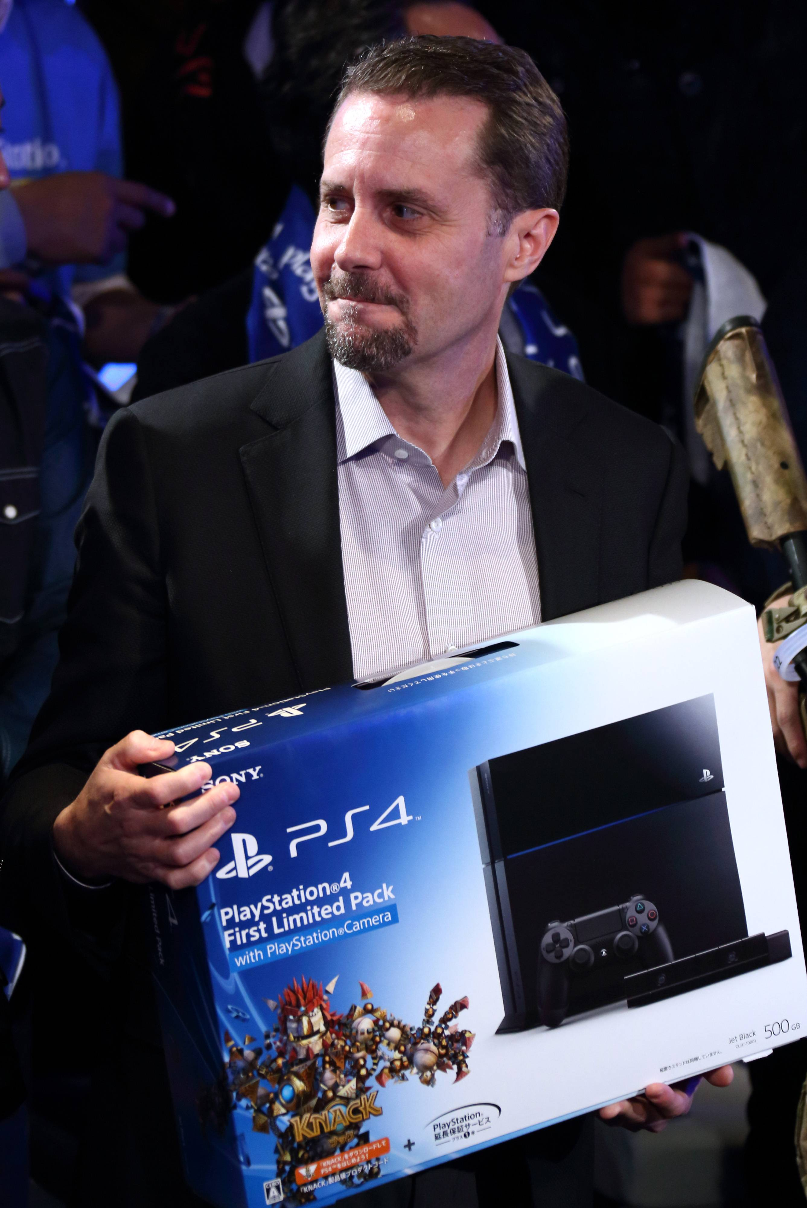 Andrew House, president and chief executive officer of Sony Computer Entertainment Inc., holds a box containing the PlayStation 4 (PS4) video game console at the launch of the PS4 console at the Sony showroom in Tokyo, Japan, on Saturday, Feb. 22, 2014. Sony Corp., its credit rating cut to junk by Moody's Investors Service as Japan's biggest television maker struggles to capture consumer demand for smartphones and tablet computers, released the PS4 console in Japan.