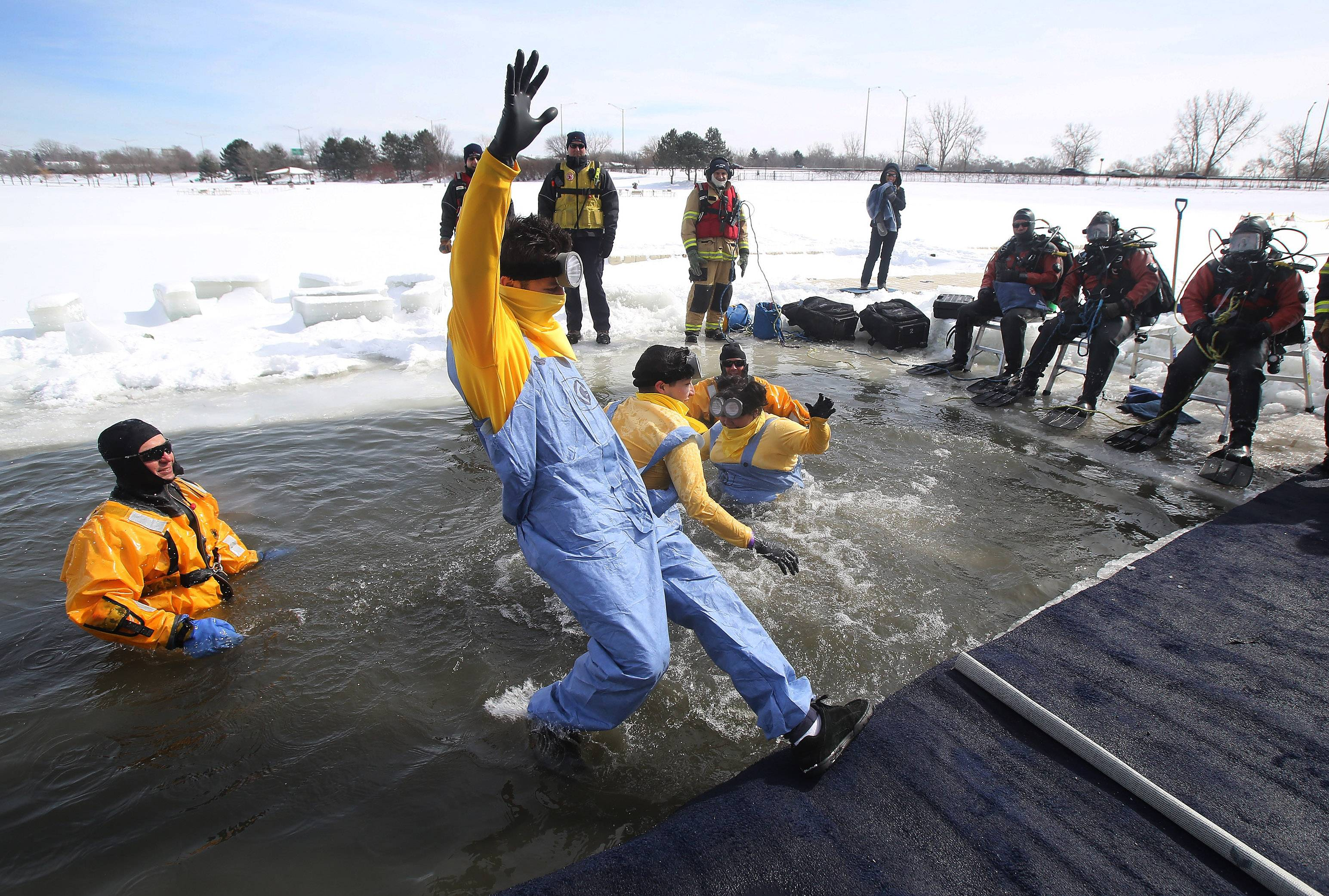 "The Palatine Fire Department Dive Rescue Team watches Sunday as Danny Solovastru of Morton Grove, dressed as a Minion from the ""Despicable Me"" movies, falls into the cold water during the Polar Plunge at Twin Lakes Recreation Area in Palatine. The event raised more than $100,000 for Special Olympics."
