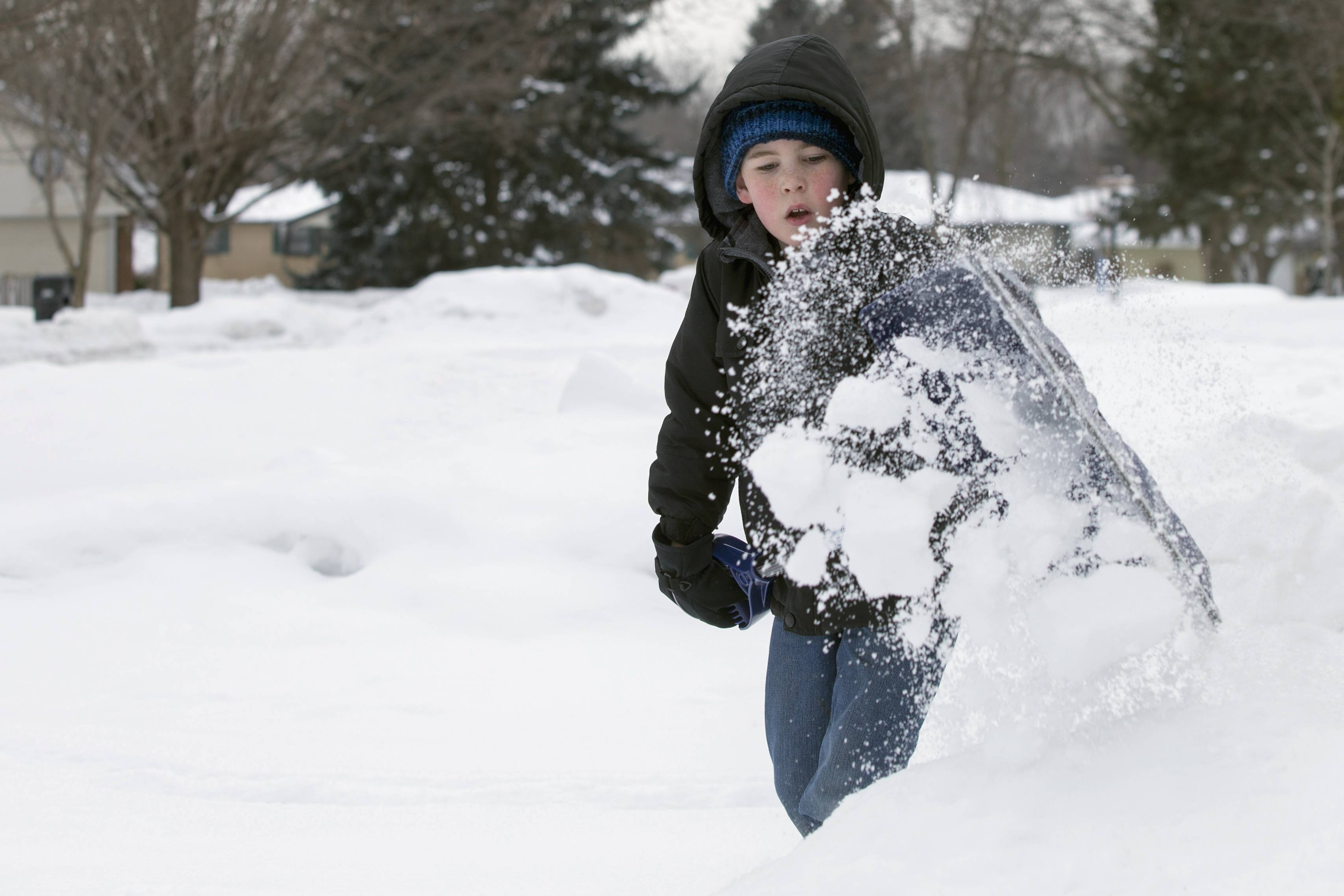 In this Feb. 12, 2014 photo, Cam Russo, 8, shovels a driveway in his neighborhood in Rockford, Ill. Russo's class was given shovels and gloves and are trying to collectively shovel 100 driveways by the end of Feb. This makes for Russo's 11th.