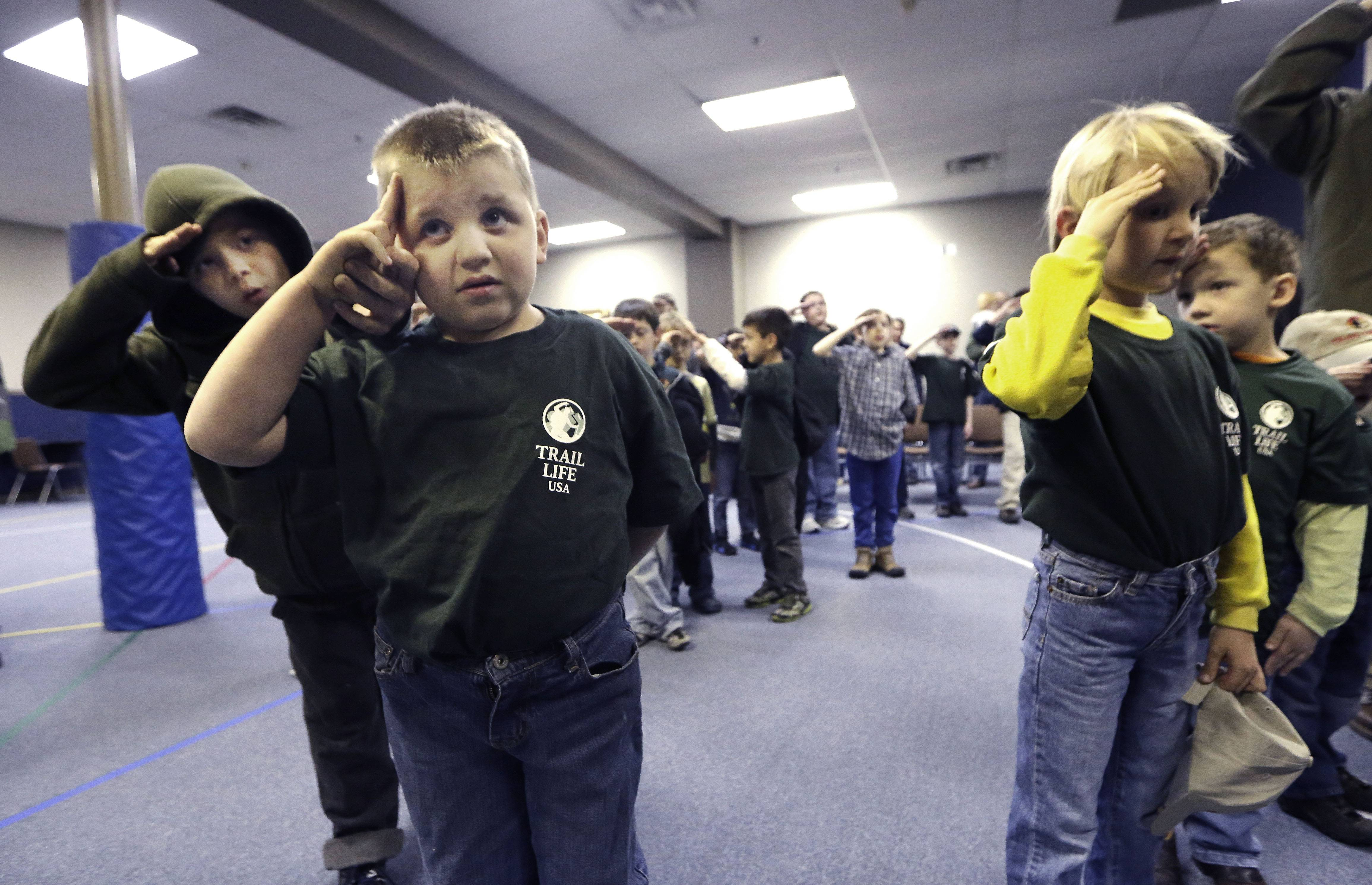 In this Tuesday, Feb. 4, 2014 photo, Trail Life member Adrian McCade, 7, second from left, gets direction on hand placement for the salute from his older brother Jack McCade, 8, during a group meeting in North Richland Hills, Texas. John Stemberger, an Orlando, Fla. lawyer who led the opposition to the Boy Scouts of America's May 2013 vote to accept openly gay youth, went on to found Trail Life.