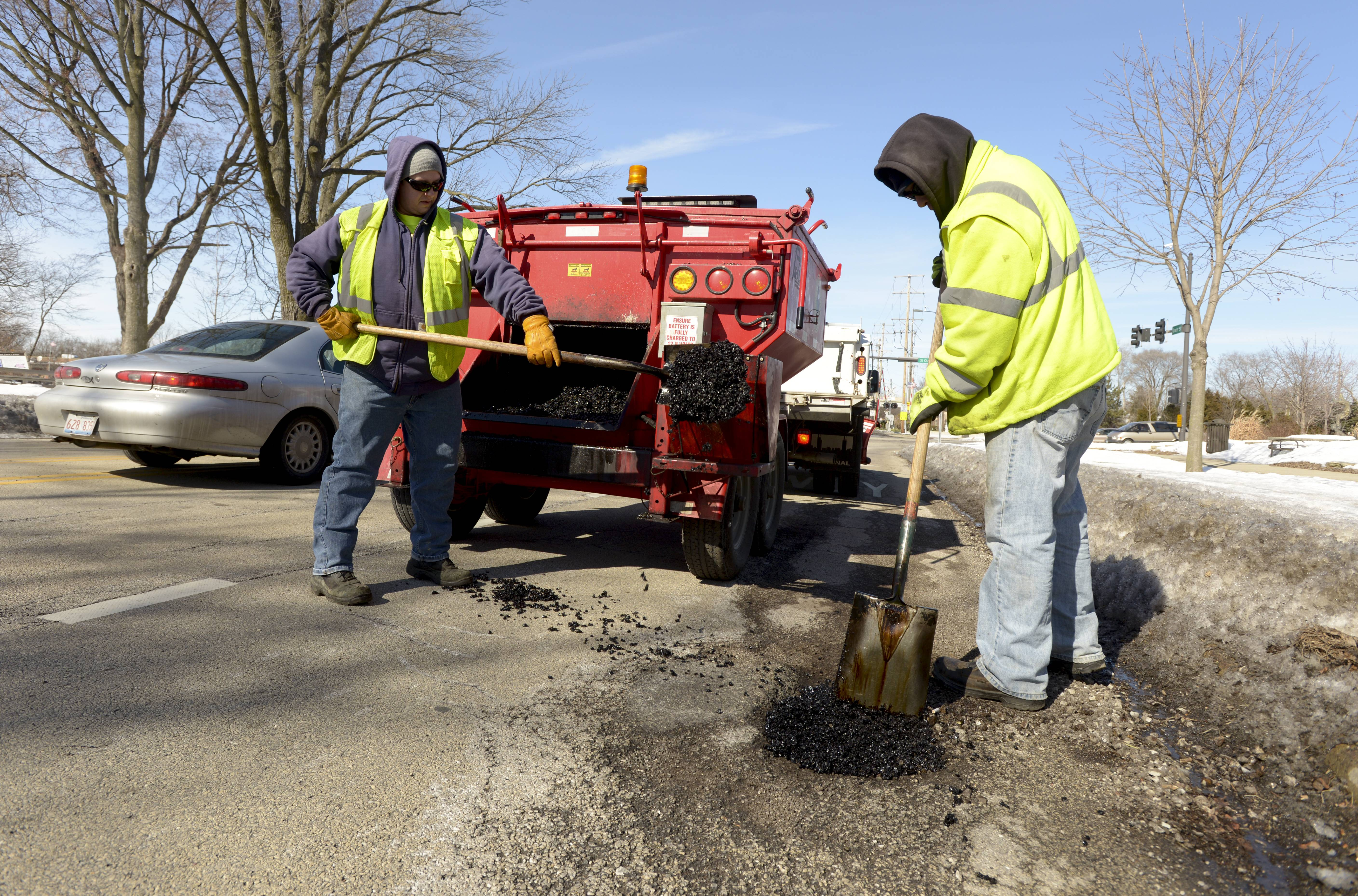 Employees from the Lombard public works fill in potholes along Grace Street in Lombard Monday afternoon. The crew said they had been filling holes all weekend with the worst of them along St. Charles Road.