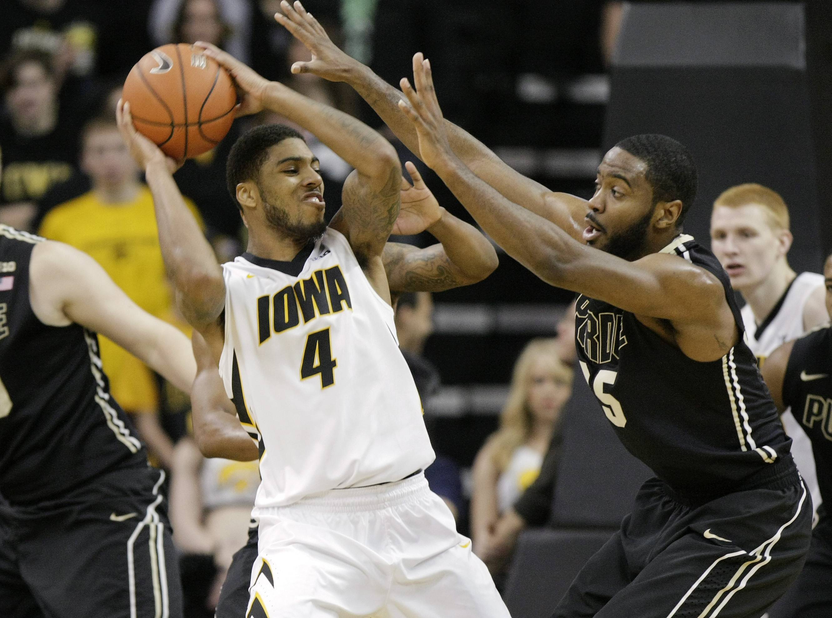 Iowa guard Roy Devyn Marble (4) is double-teamed by Purdue guard Rapheal Davis, right, and guard Ronnie Johnson, behind Marble, during the first half of a Big Ten NCAA college basketball game at Carver-Hawkeye Arena on Sunday, March 2, 2014, in Iowa City, Iowa.