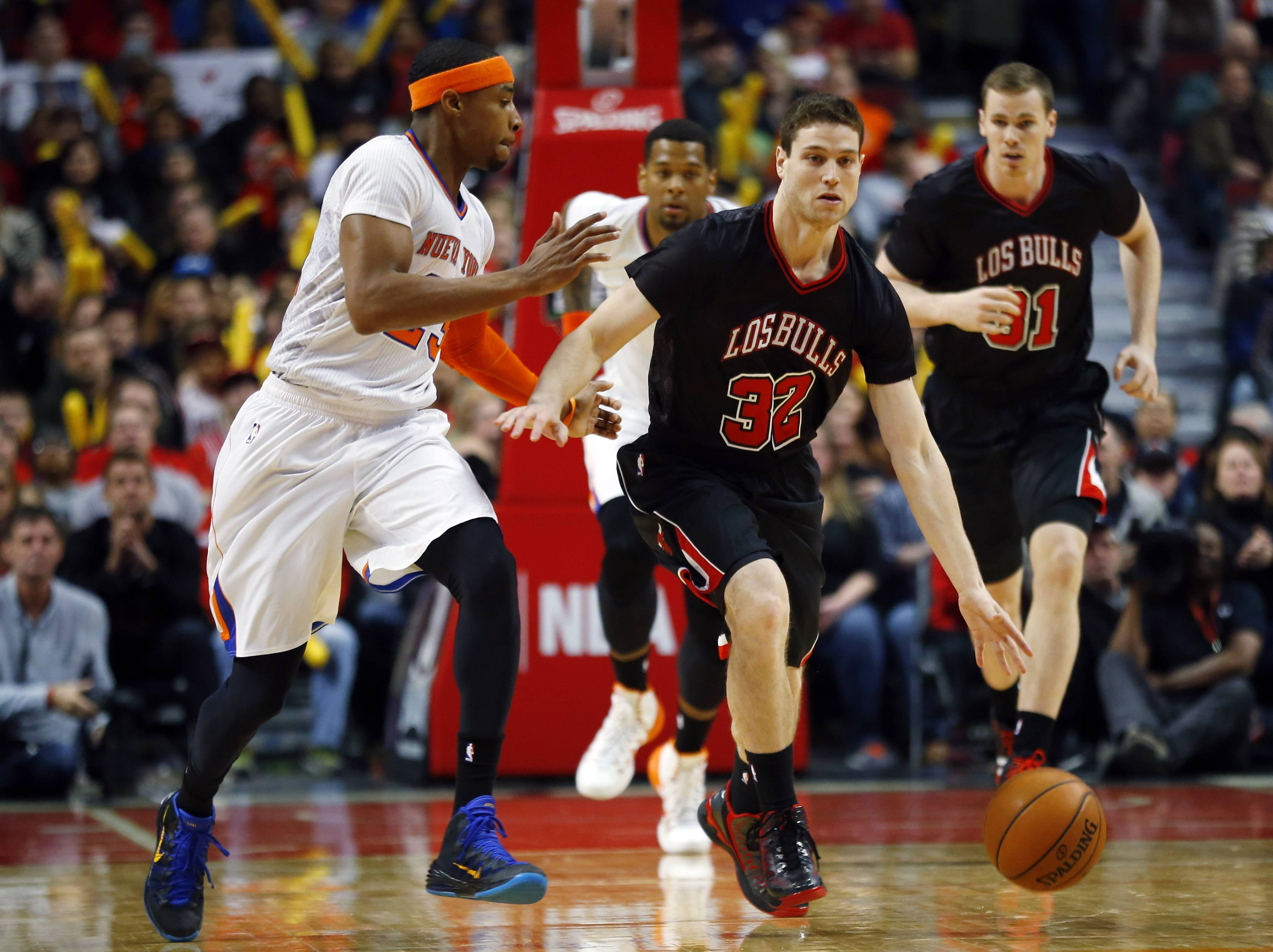 Newly signed Bulls guard Jimmer Fredette dribbles past New York Knicks guard Toure' Murry during the second half of an NBA basketball game on Sunday, March 2, 2014, in Chicago.