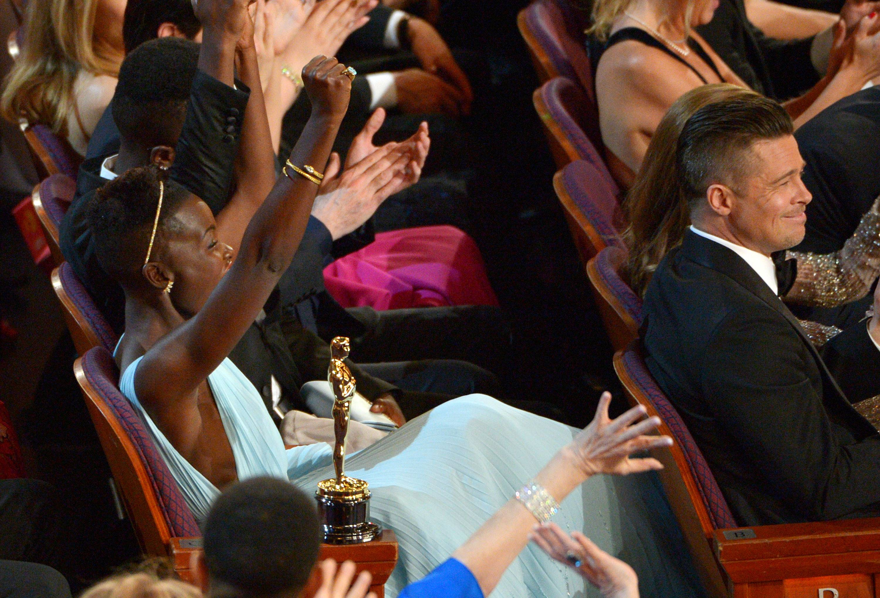 "Lupita Nyong'o celebrates in the audience after ""12 Years a Slave"" is announced as winner of the award for best picture of the year during the Oscars."