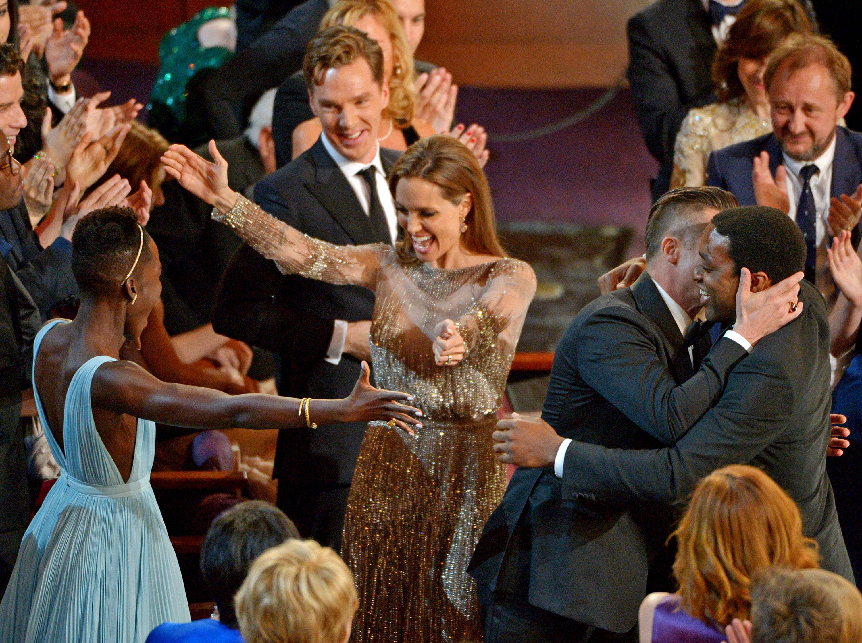 "Lupita Nyong'o, left, prepares to embrace Angelina Jolie, as Benedict Cumberbatch, background center, looks on, and Brad Pitt, embraces Chiwetel Ejiofor, right, after ""12 Years a Slave"" was announced the winner for best picture."