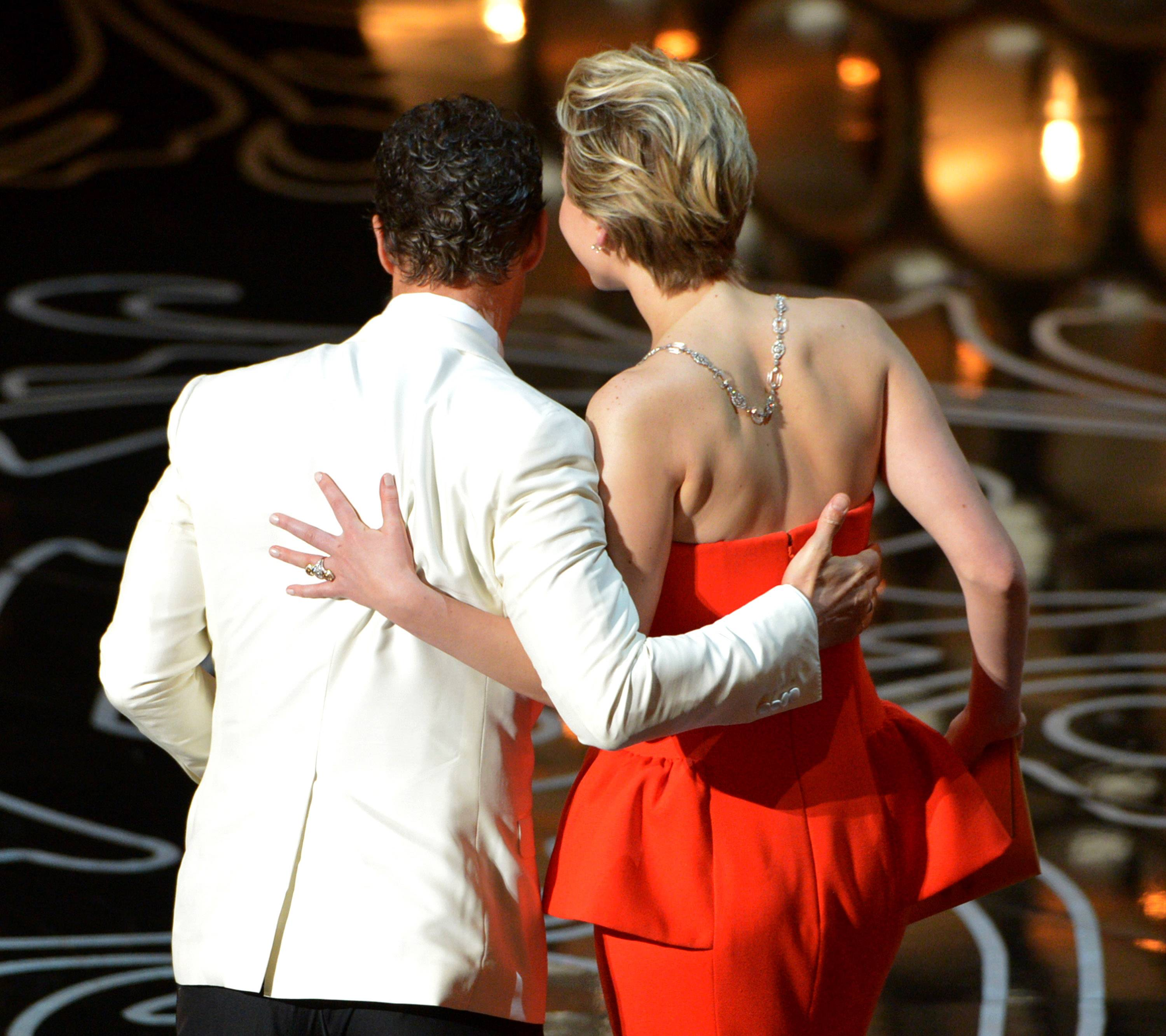 Matthew McConaughey and Jennifer Lawrence walk off stage during the Oscars.
