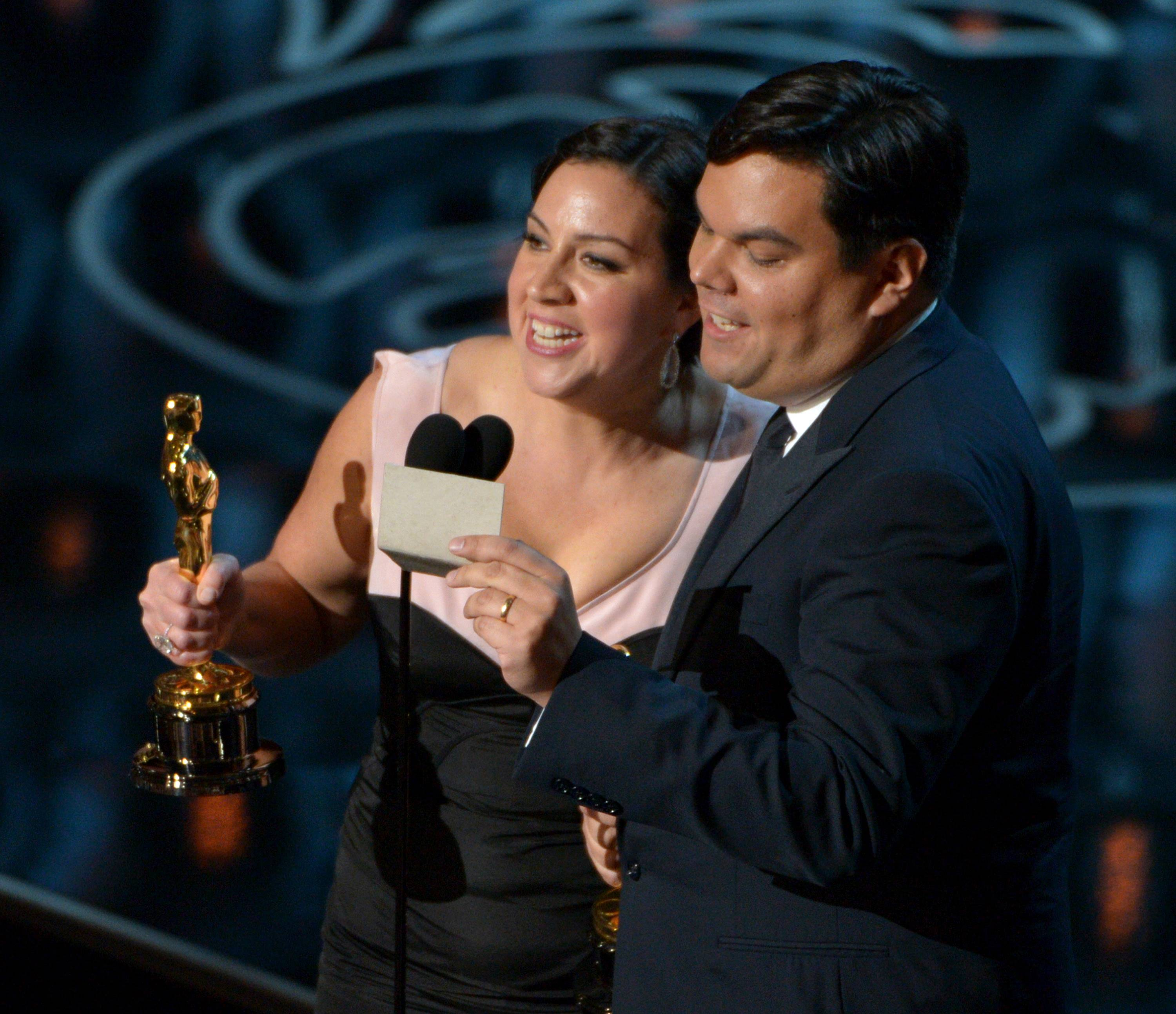 "Kristen Anderson-Lopez, left, and Robert Lopez accept the award for an original song in a feature film for ""Let It Go"" from ""Frozen."""
