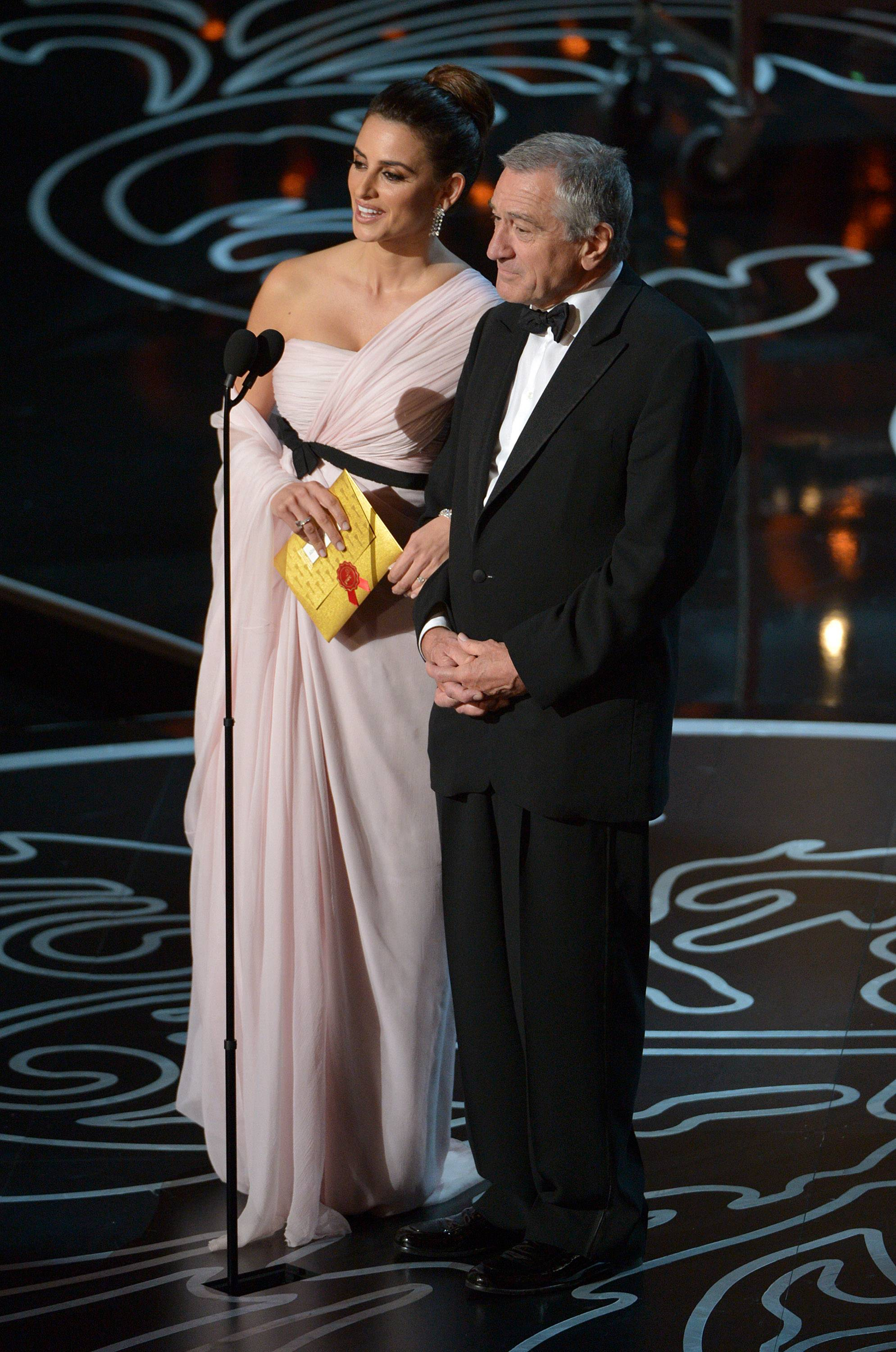 Penelope Cruz, left, and Robert De Niro speak on stage before presenting an award during the Oscars.