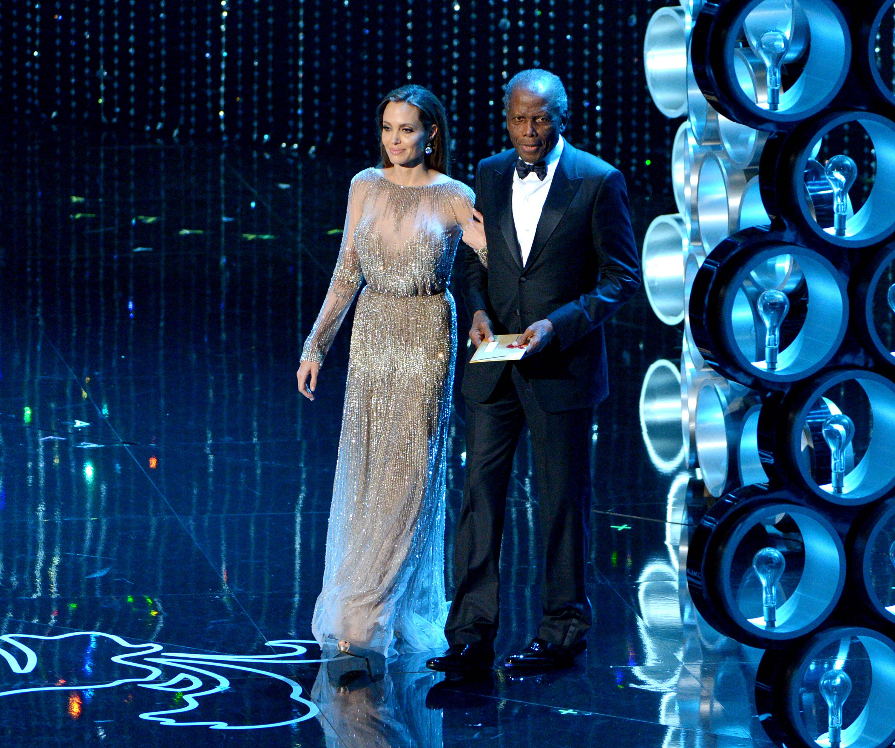 Angelina Jolie and Sidney Poitier walk on stage to present the award for best director during the Oscars.