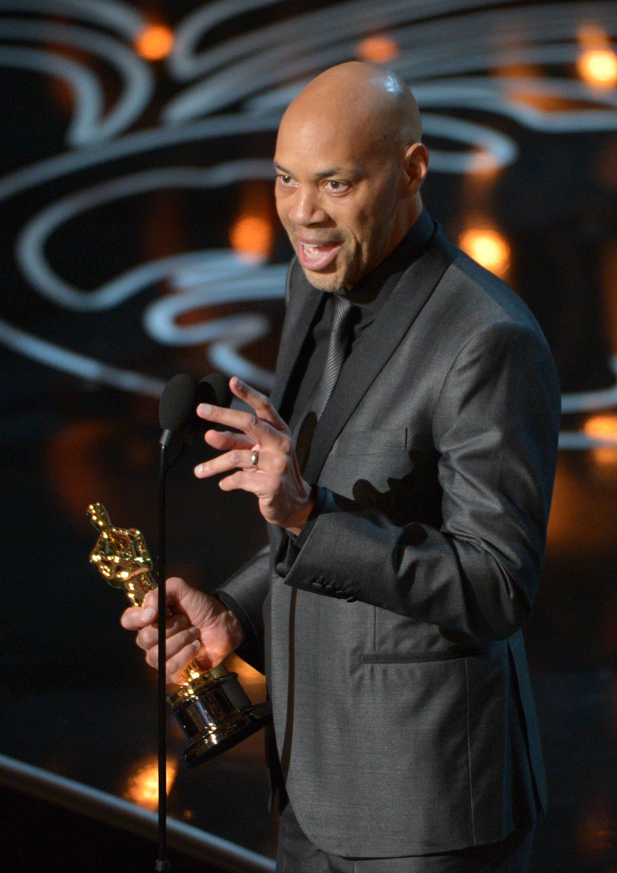 "John Ridley accepts the award for the best adapted screenplay of the year for ""12 Years a Slave."""