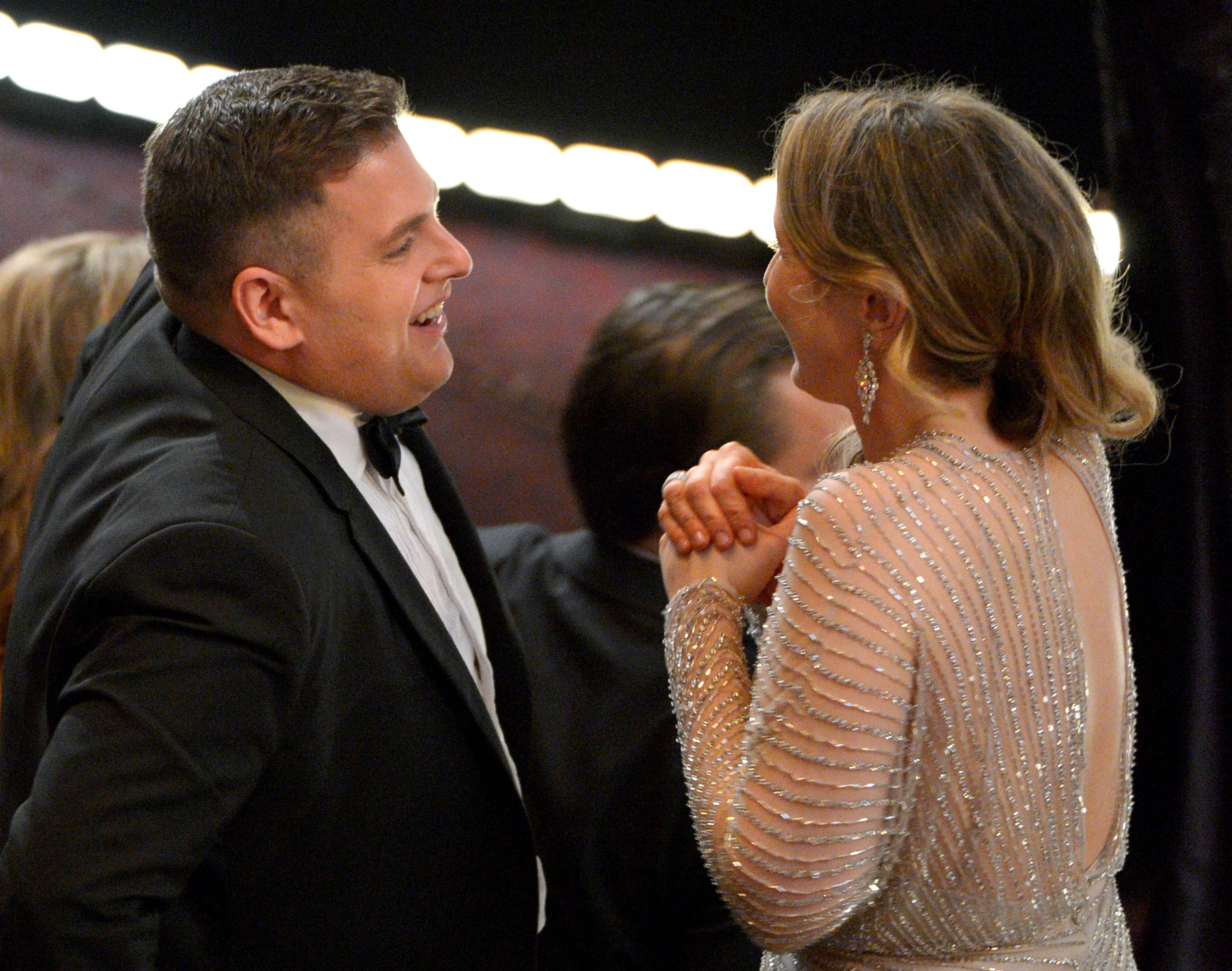 Jonah Hill, left, and Julie Delpy speak in the audience at the Oscars at the Dolby Theatre on Sunday in Los Angeles.