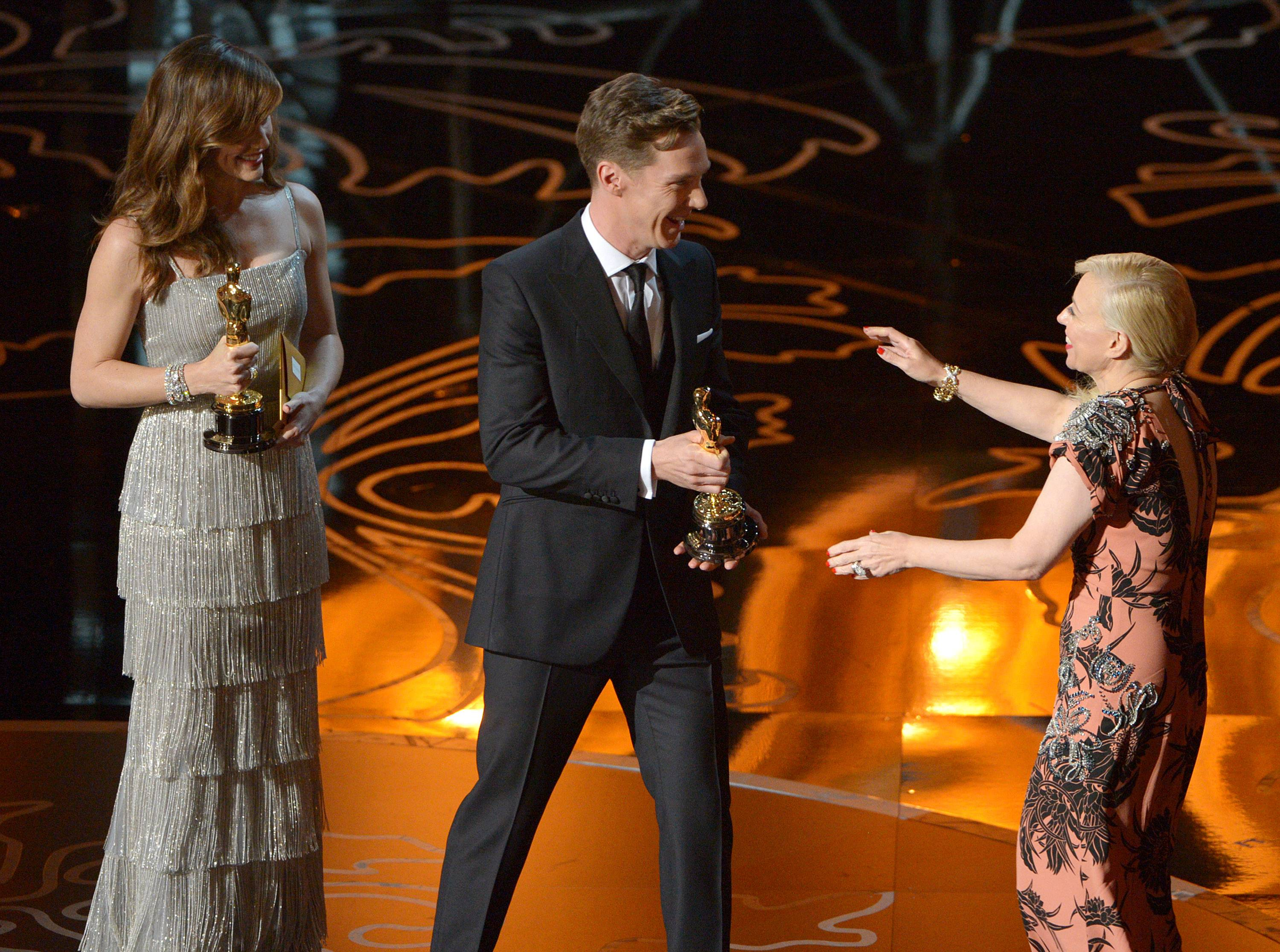 "Presenters Jennifer Garner, left, and Benedict Cumberbatch, center, present Catherine Martin with the award for best production design for ""The Great Gatsby"" on stage."