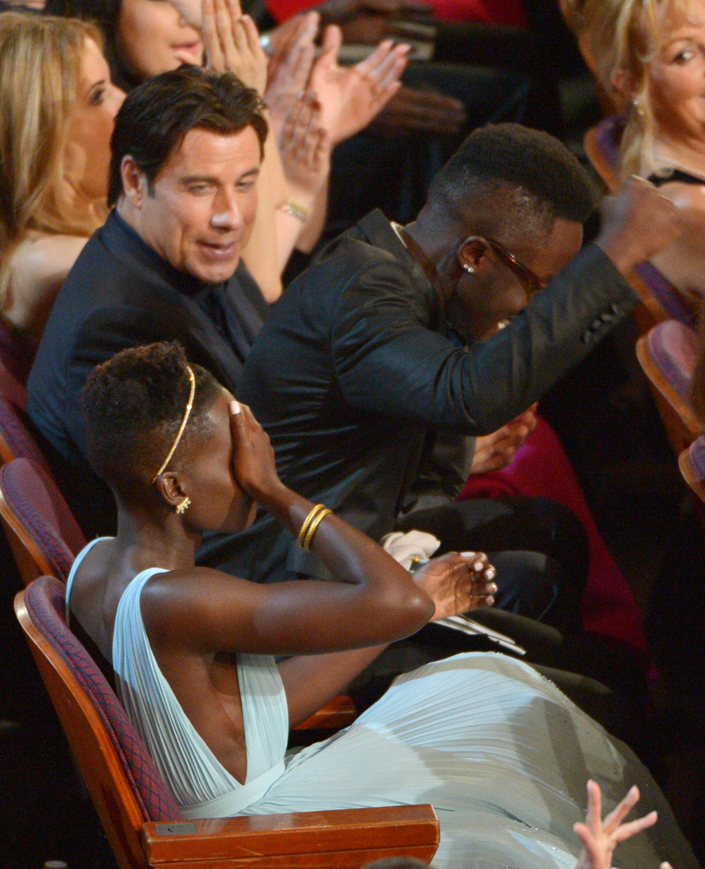 "Lupita Nyong'o reacts to winning the award for best actress in a supporting role for ""12 Years a Slave"" as she sits next to her brother Peter and actor John Travolta in the audience."