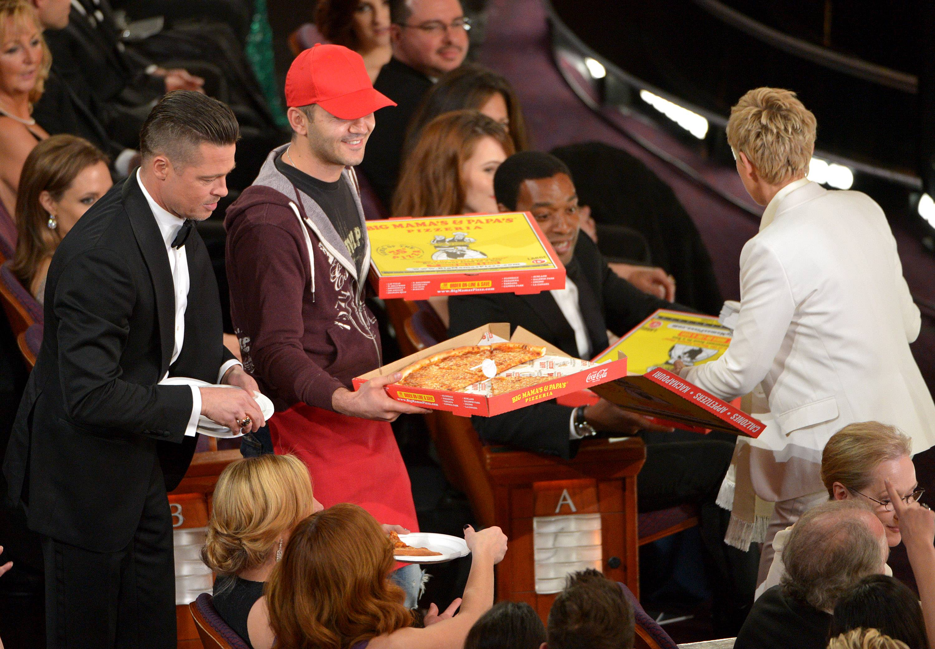 Brad Pitt, left, and Ellen DeGeneres, right, pass out pizza in the audience during the Oscars.