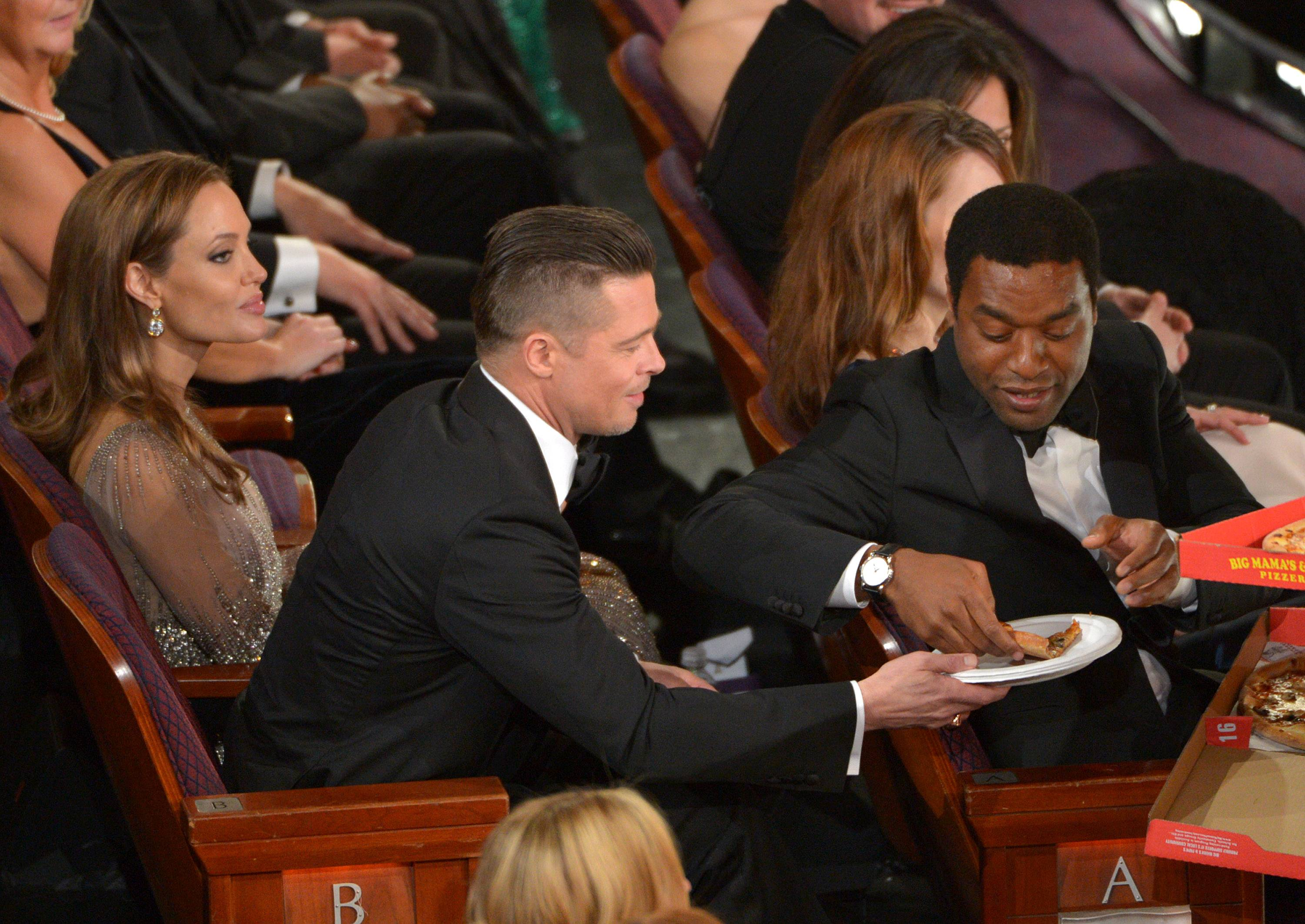 Angelina Jolie, left, looks on as Brad Pitt shares a slice of pizza with Chiwetel Ejiofor in the audience.