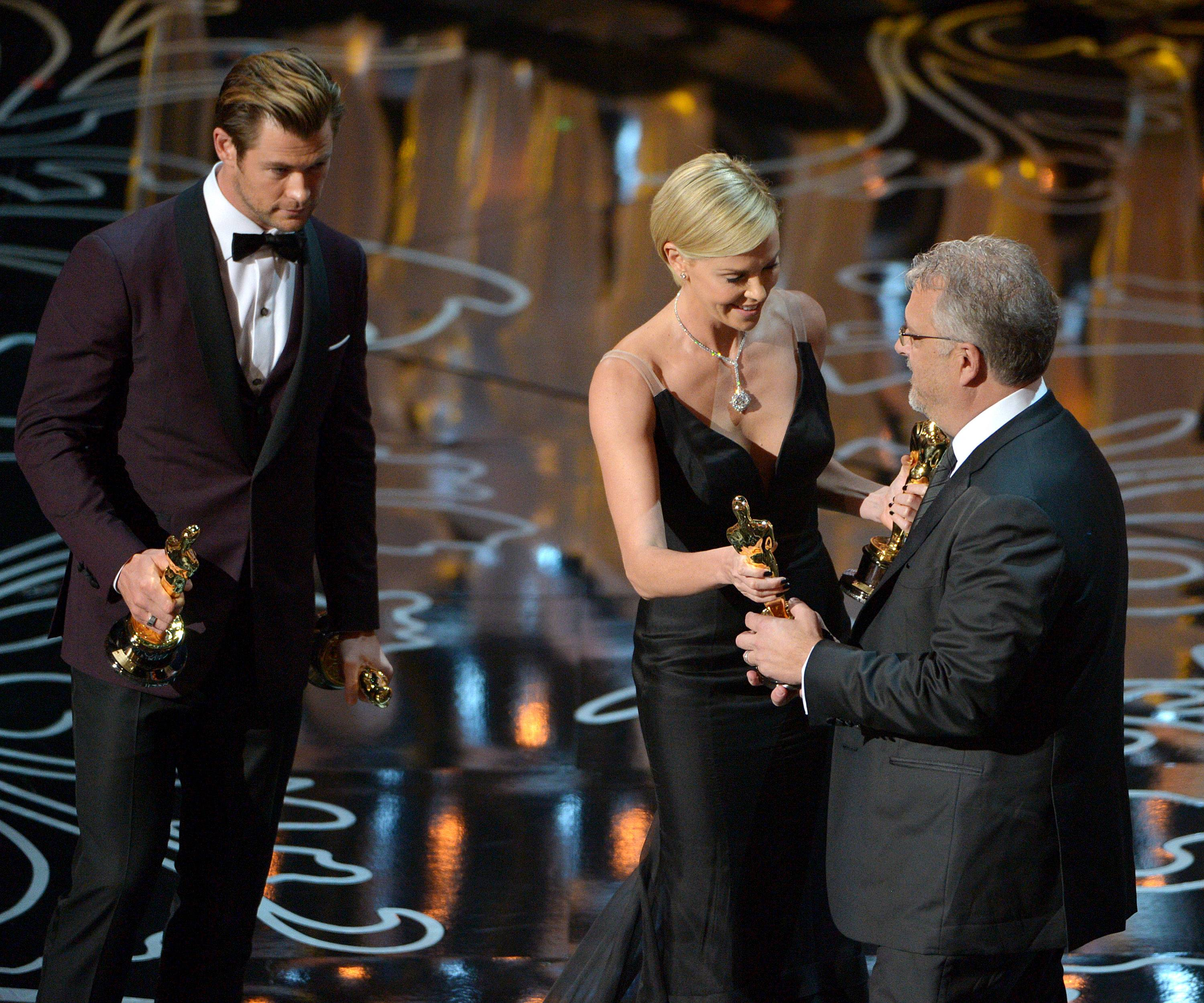 "Presenters Chris Hemsworth, left, and Charlize Theron, center, present Skip Lievsay with the award for best sound mixing for ""Gravity."""