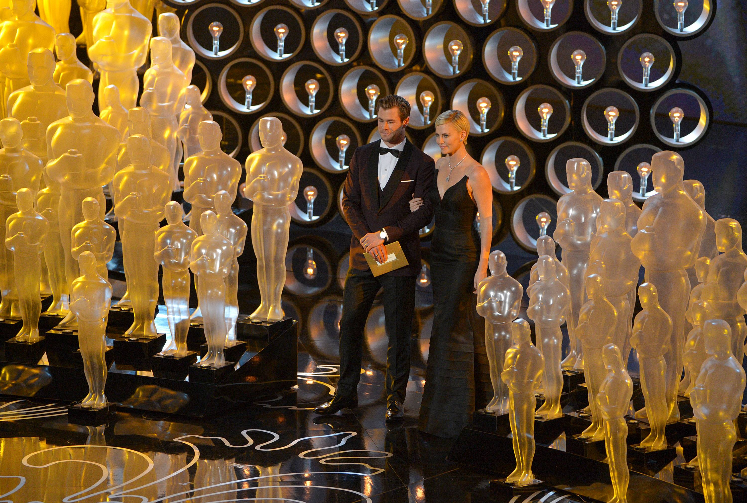 Chris Hemsworth, left, and Charlize Theron speak on stage during the Oscars.