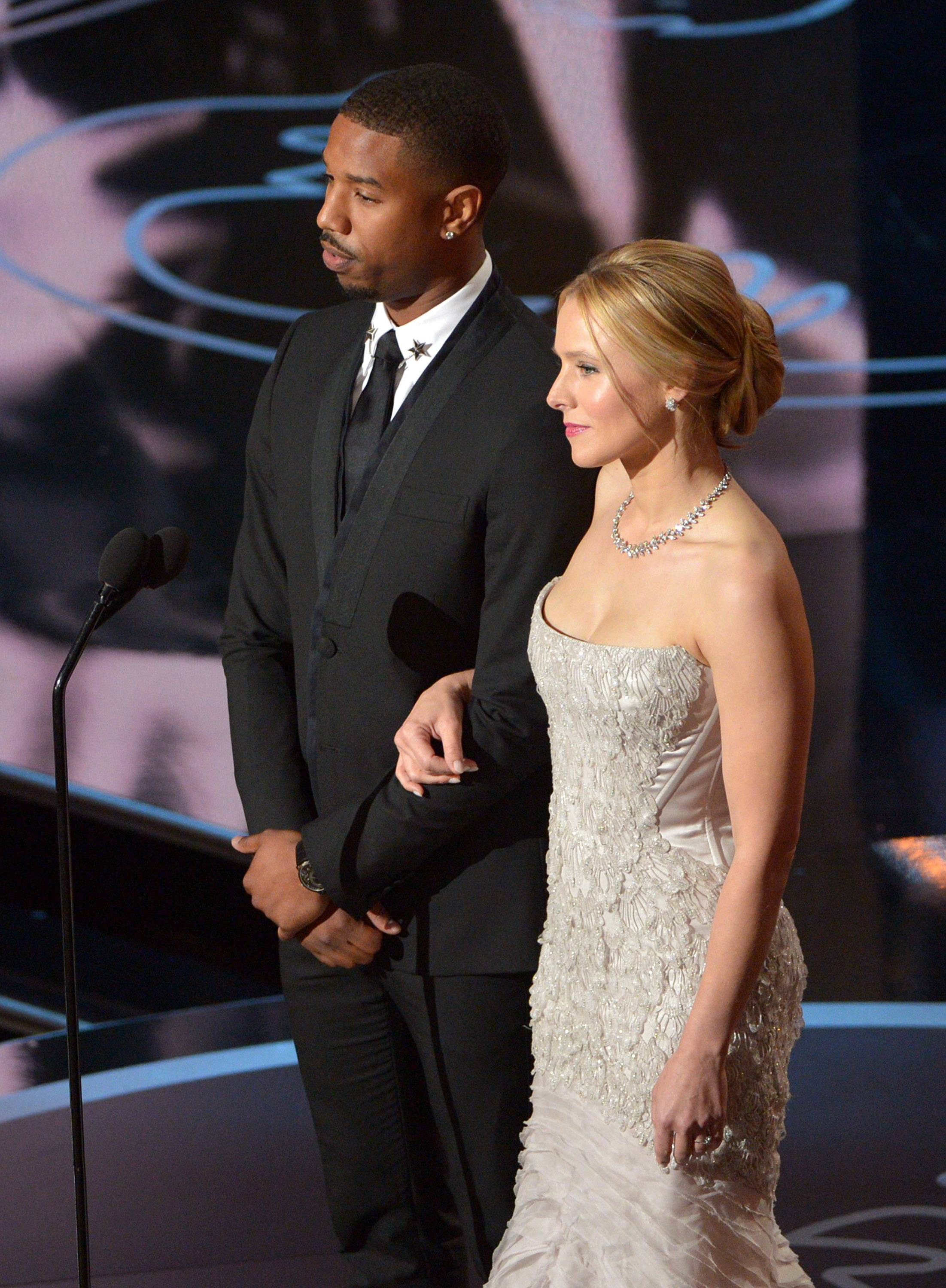Michael B. Jordan, left, and Kristen Bell speak during the Oscars.