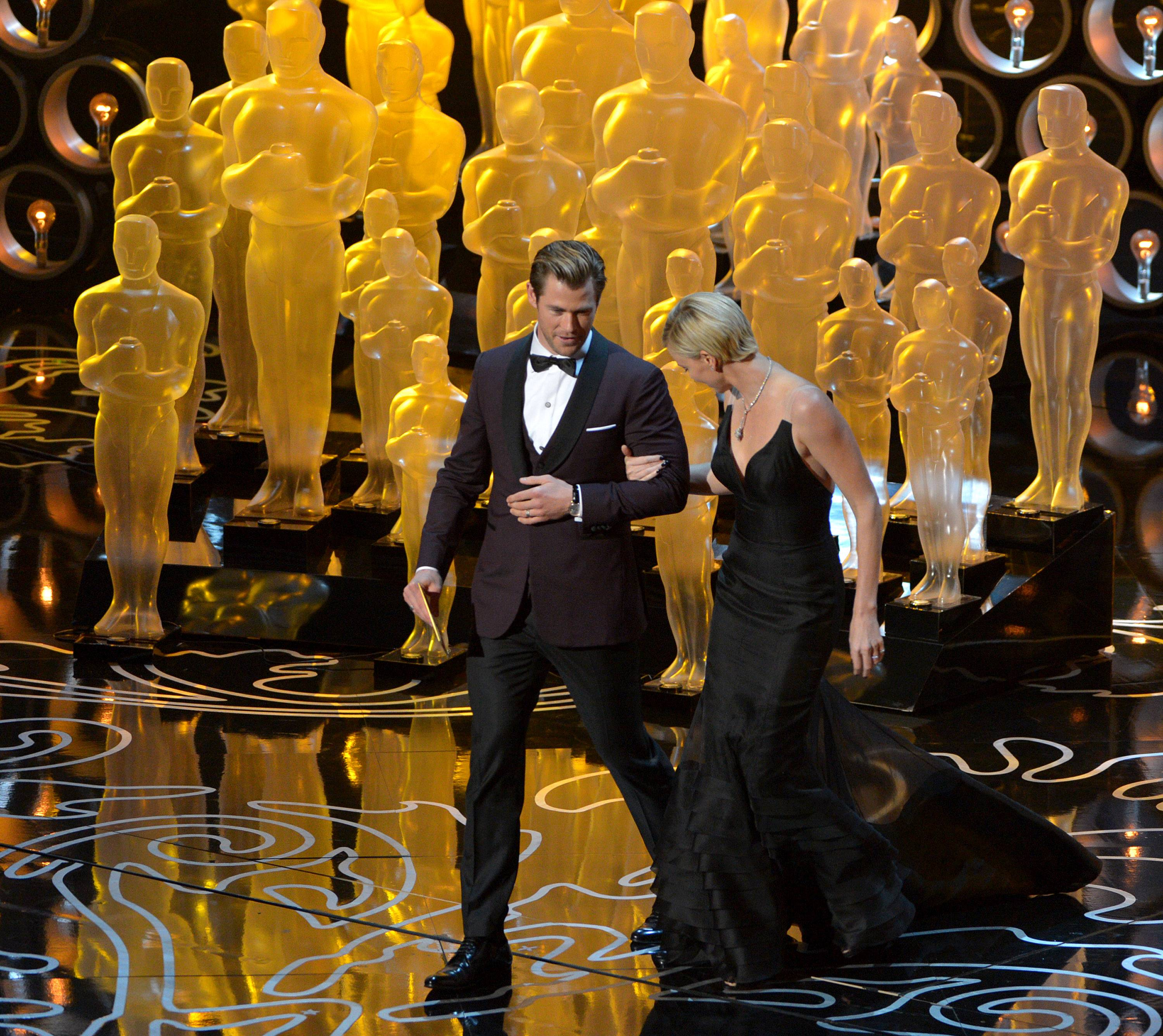 Chris Hemsworth, left, and Charlize Theron walk on stage during the Oscars.