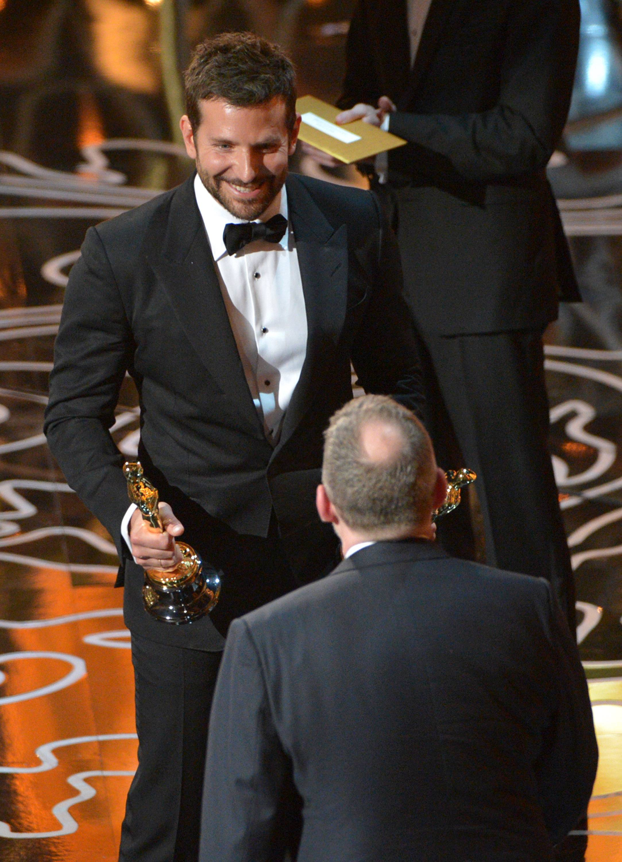 "Bradley Cooper, left, presents Morgan Neville with the award for best documentary feature of the year for ""20 Feet from Stardom."""