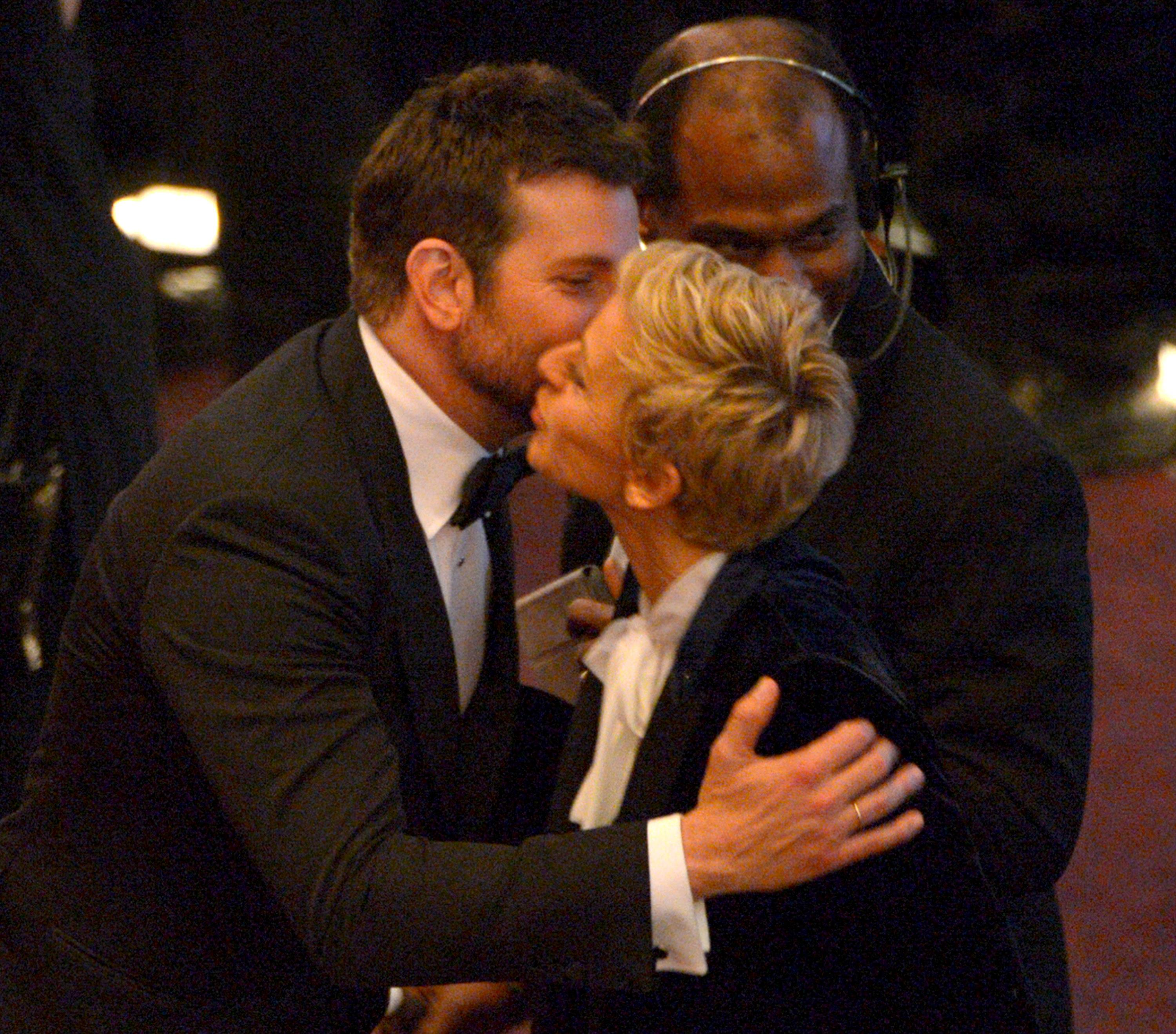 Bradley Cooper and Ellen DeGeneres kiss in the audience during the Oscars.