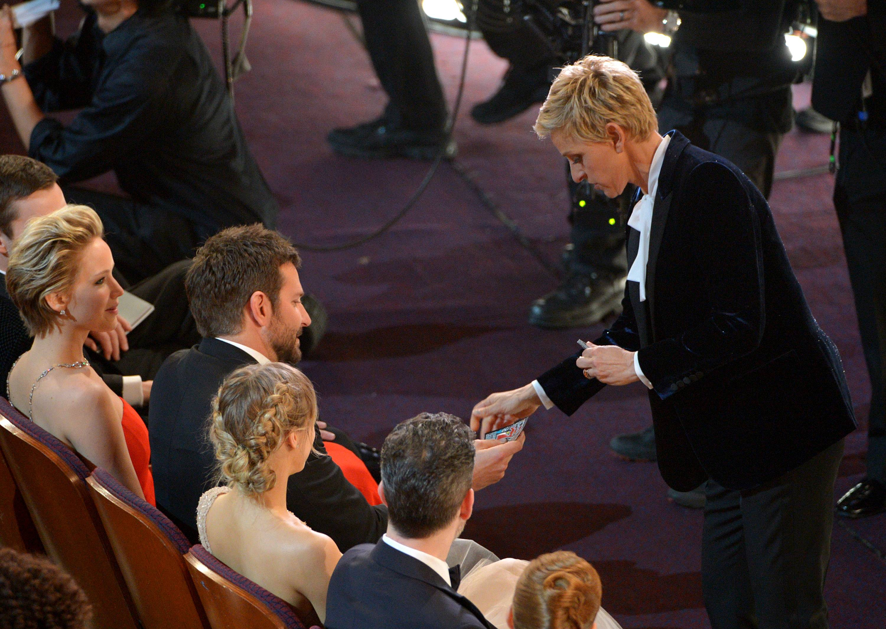Ellen DeGeneres, right, gives Bradley Cooper a lottery ticket during the Oscars.