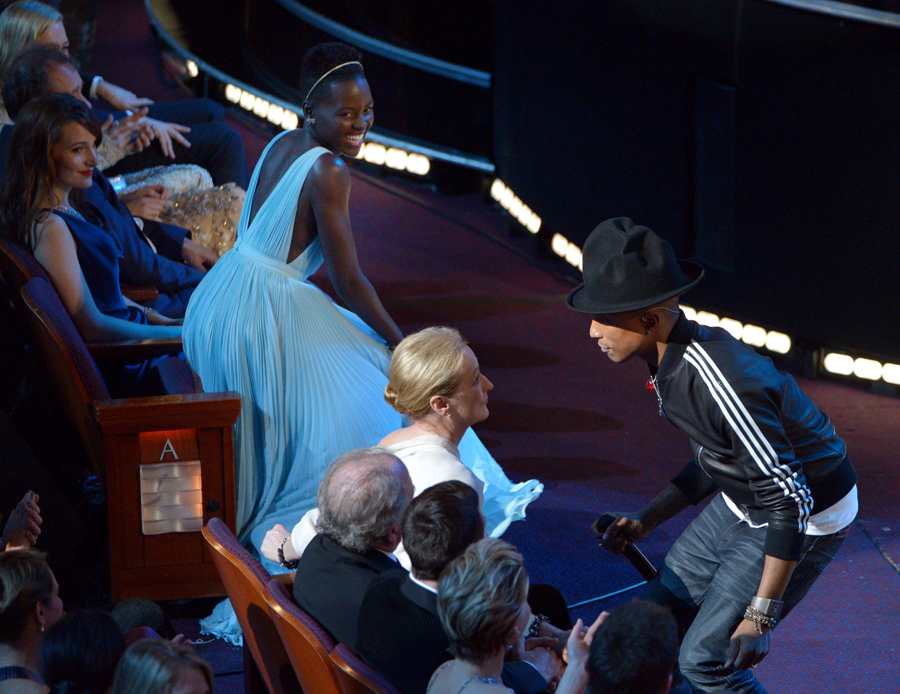 "Lupita Nyong'o , left, looks on as Meryl Streep dances with Pharrell Williams during his performance of ""Happy"" at the Oscars."