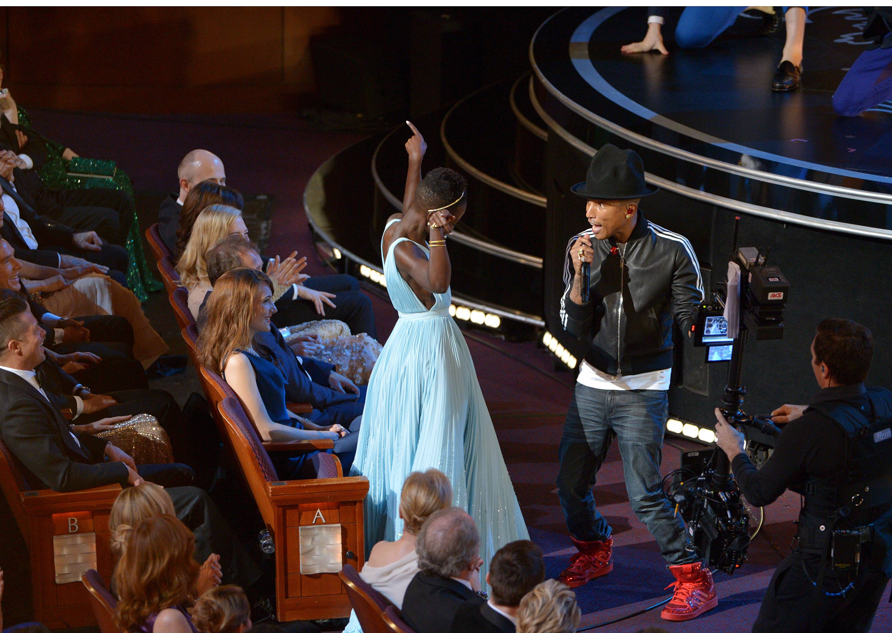 "Lupita Nyong'o, left, dances along with Pharrell Williams during his performance of ""Happy."""