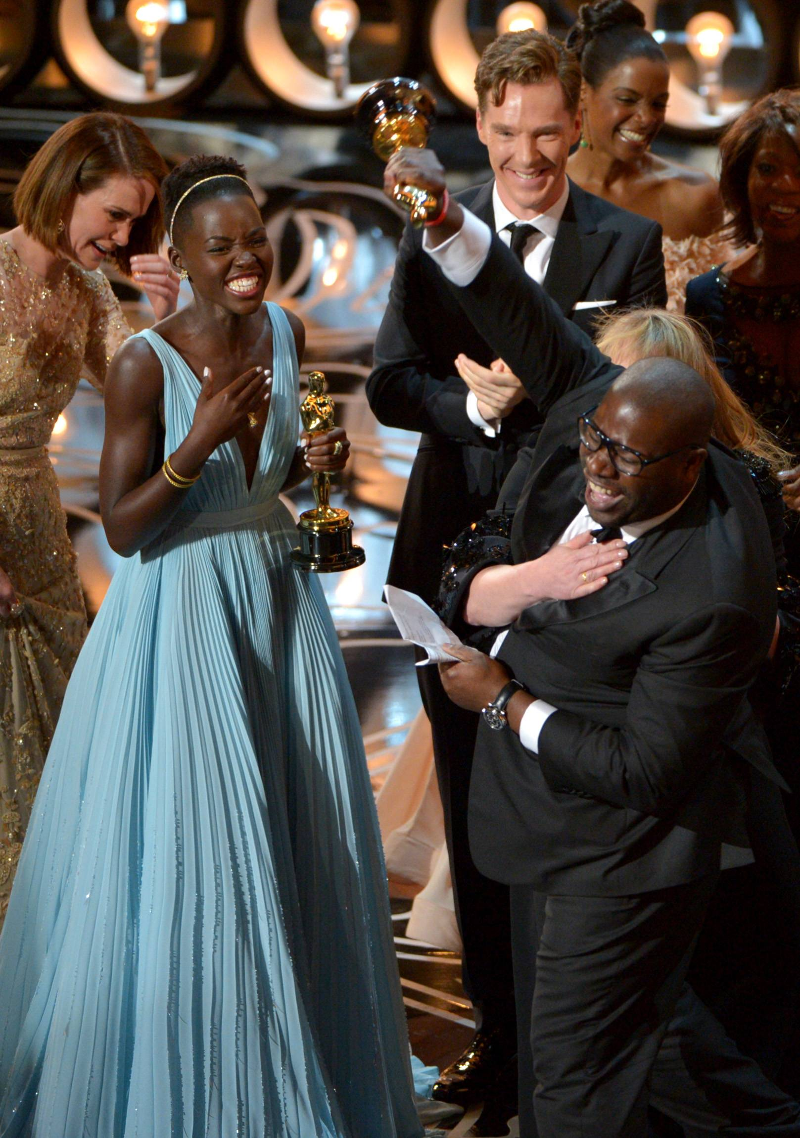"Lupita Nyong'o, left, and director Steve McQueen celebrate on stage as they accept the award for best picture of the year for ""12 Years a Slave."""