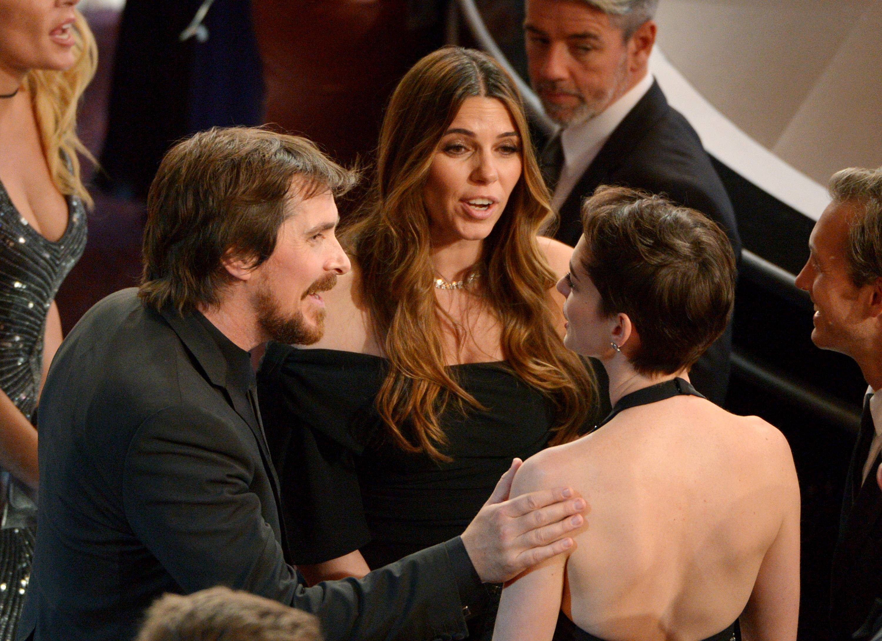 Christian Bale, left, and his wife Sibi Blazic, talk with Anne Hathaway, right, in the audience at the Oscars.
