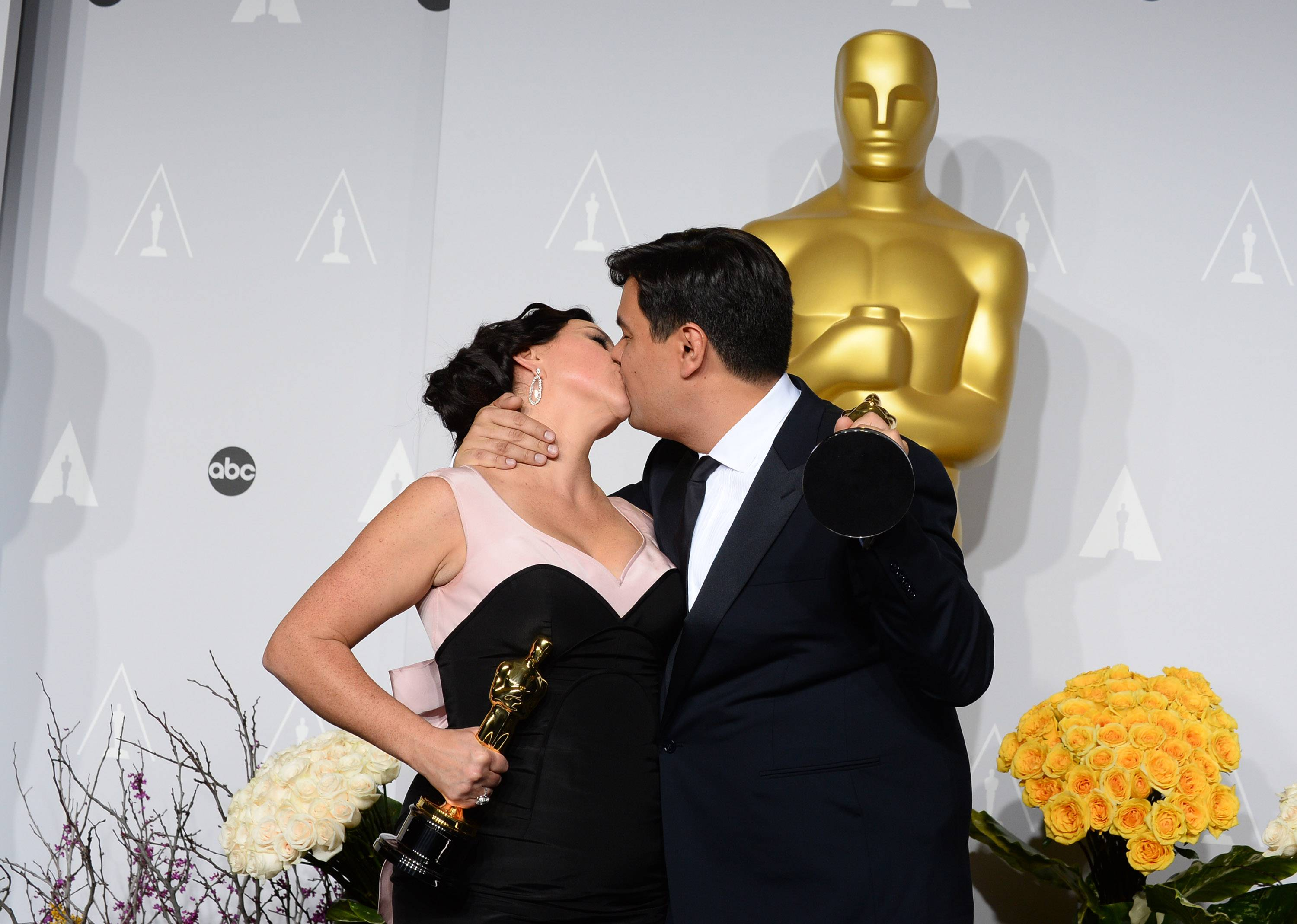 "Kristen Anderson-Lopez, left, and Robert Lopez kiss in the press room with their awards for best original song in a feature film for ""Let It Go"" from ""Frozen."""