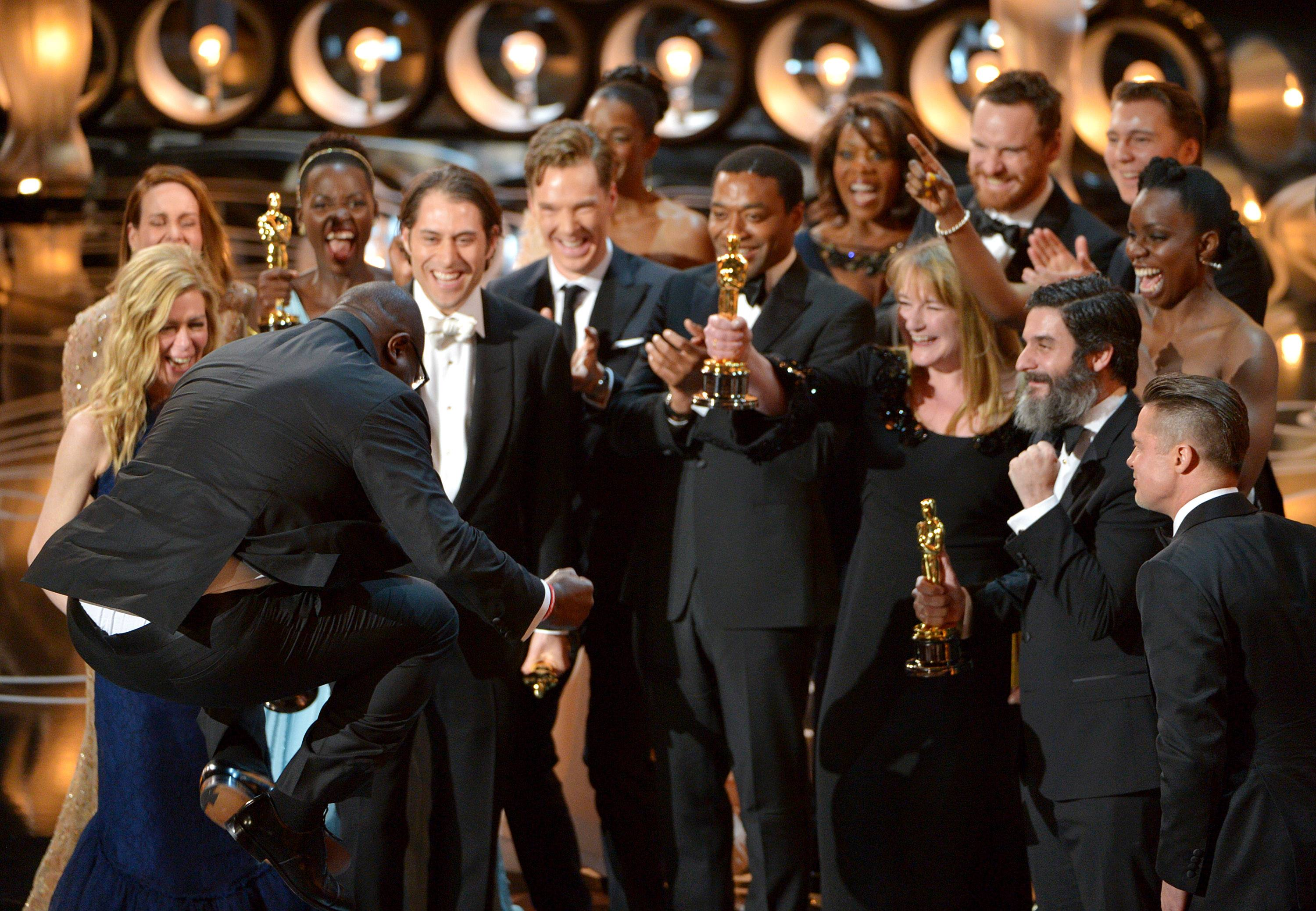 "Director Steve McQueen, left, celebrates with the cast and crew of ""12 Years a Slave"" as they accept the award for best picture during the Oscars at the Dolby Theatre on Sunday in Los Angeles."