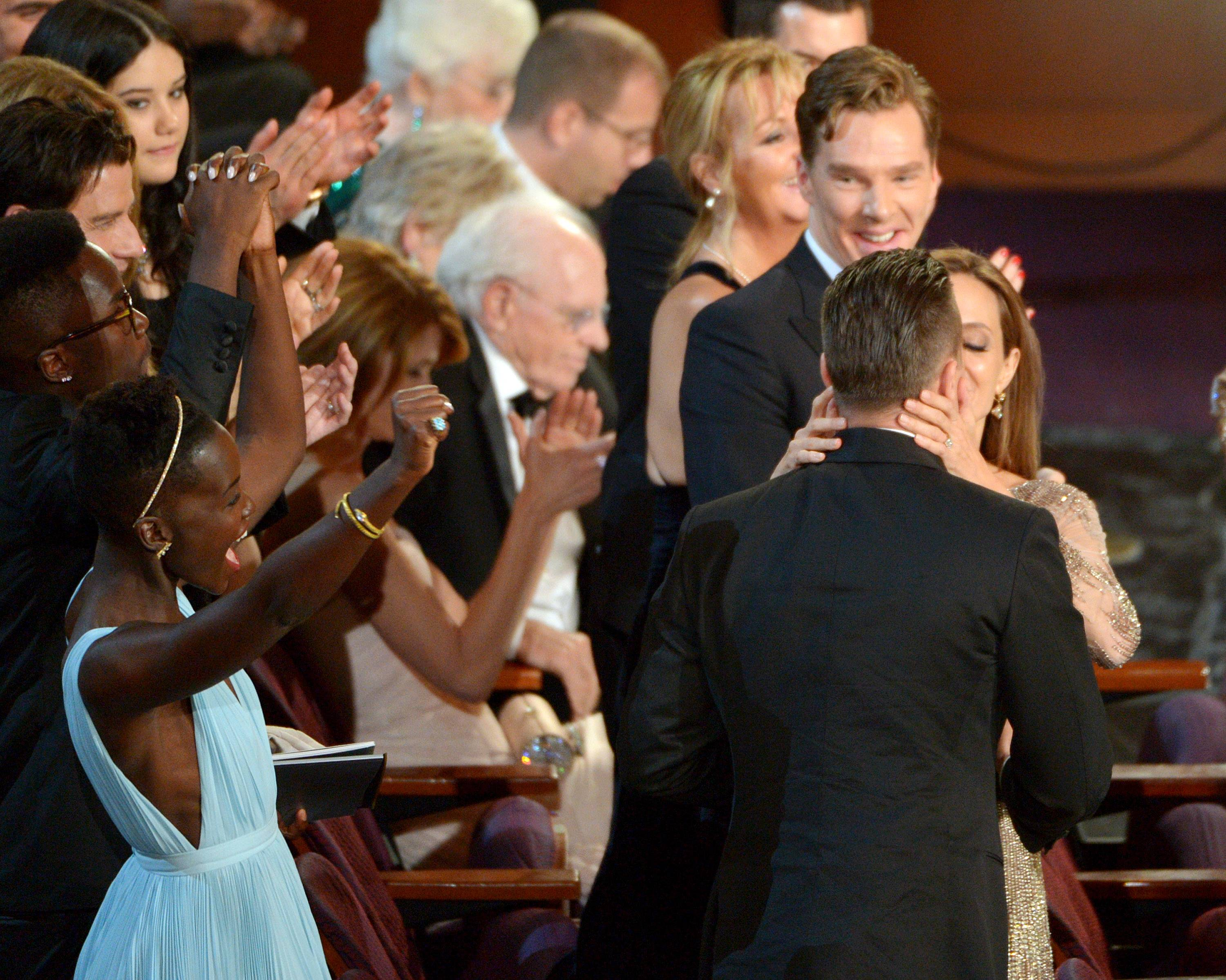 "Lupita Nyong'o, from left, Brad Pitt, and Angelina Jolie celebrate in the audience after ""12 Years a Slave"" is announced as winner of the award for best picture of the year during the Oscars."