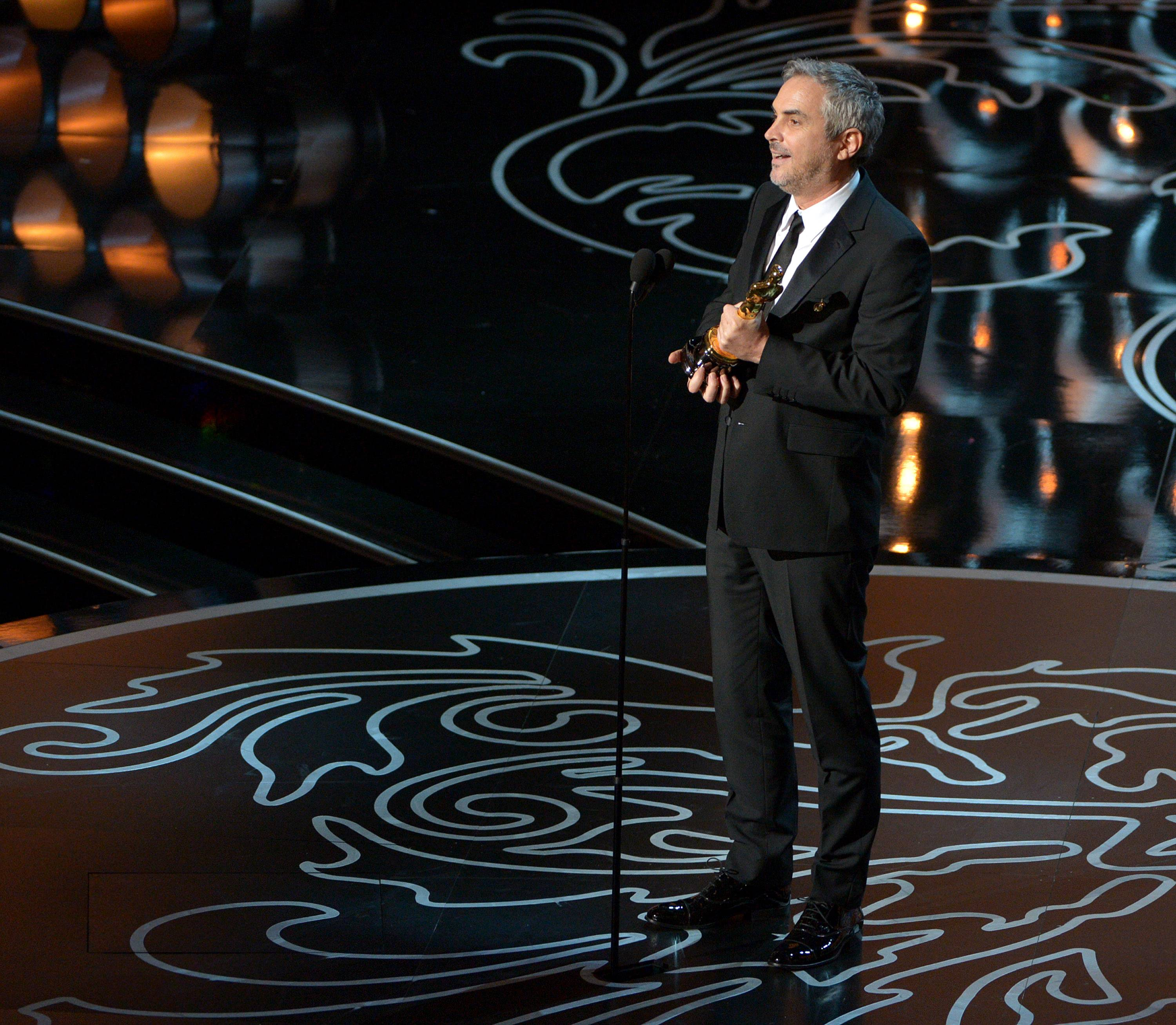 "Alfonso Cuaron accepts the award for best director of the year for ""Gravity"" during the Oscars at the Dolby Theatre on Sunday in Los Angeles."