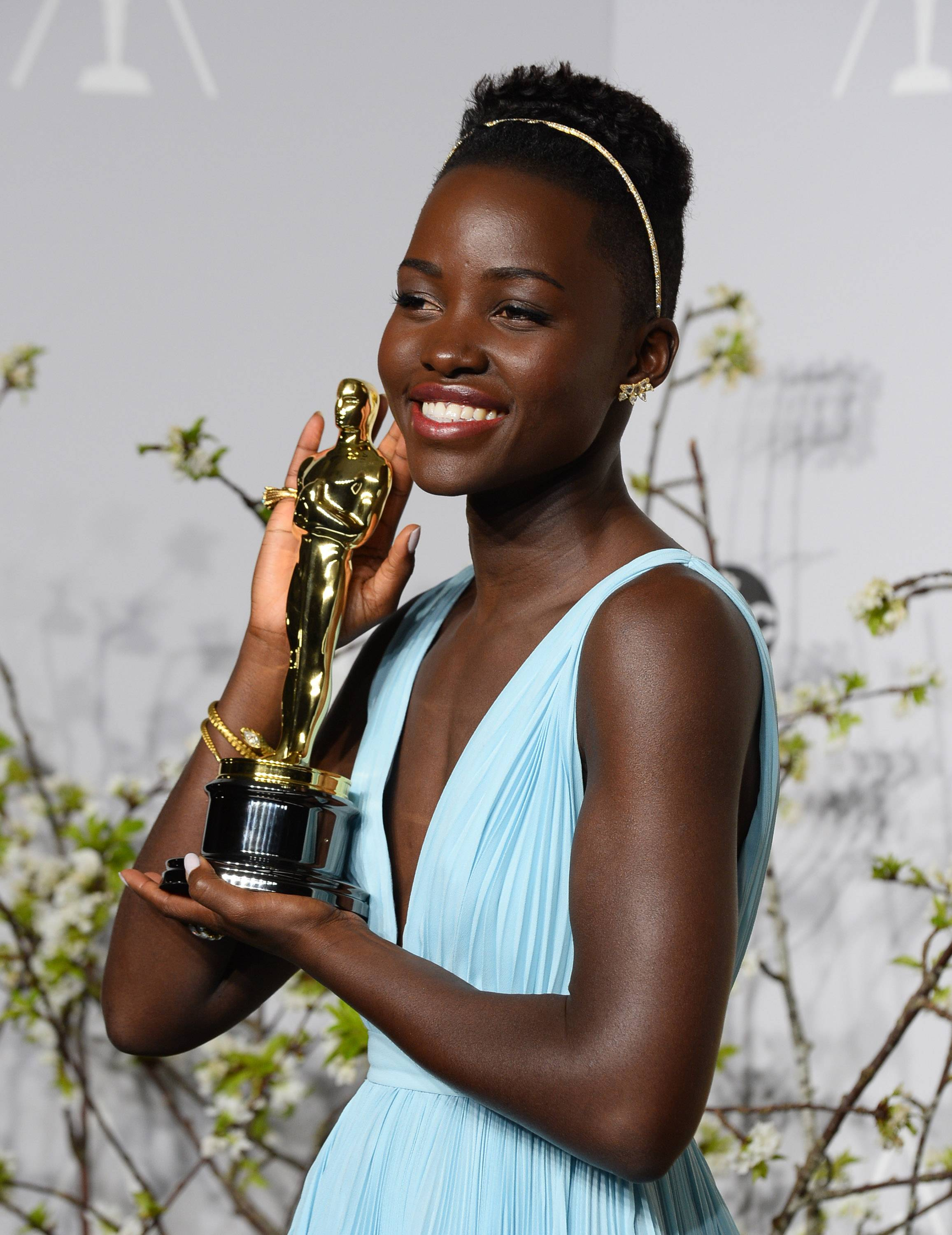"Lupita Nyong'o poses in the press room with the award for best actress in a supporting role for ""12 Years a Slave"" during the Oscars at the Dolby Theatre on Sunday in Los Angeles."
