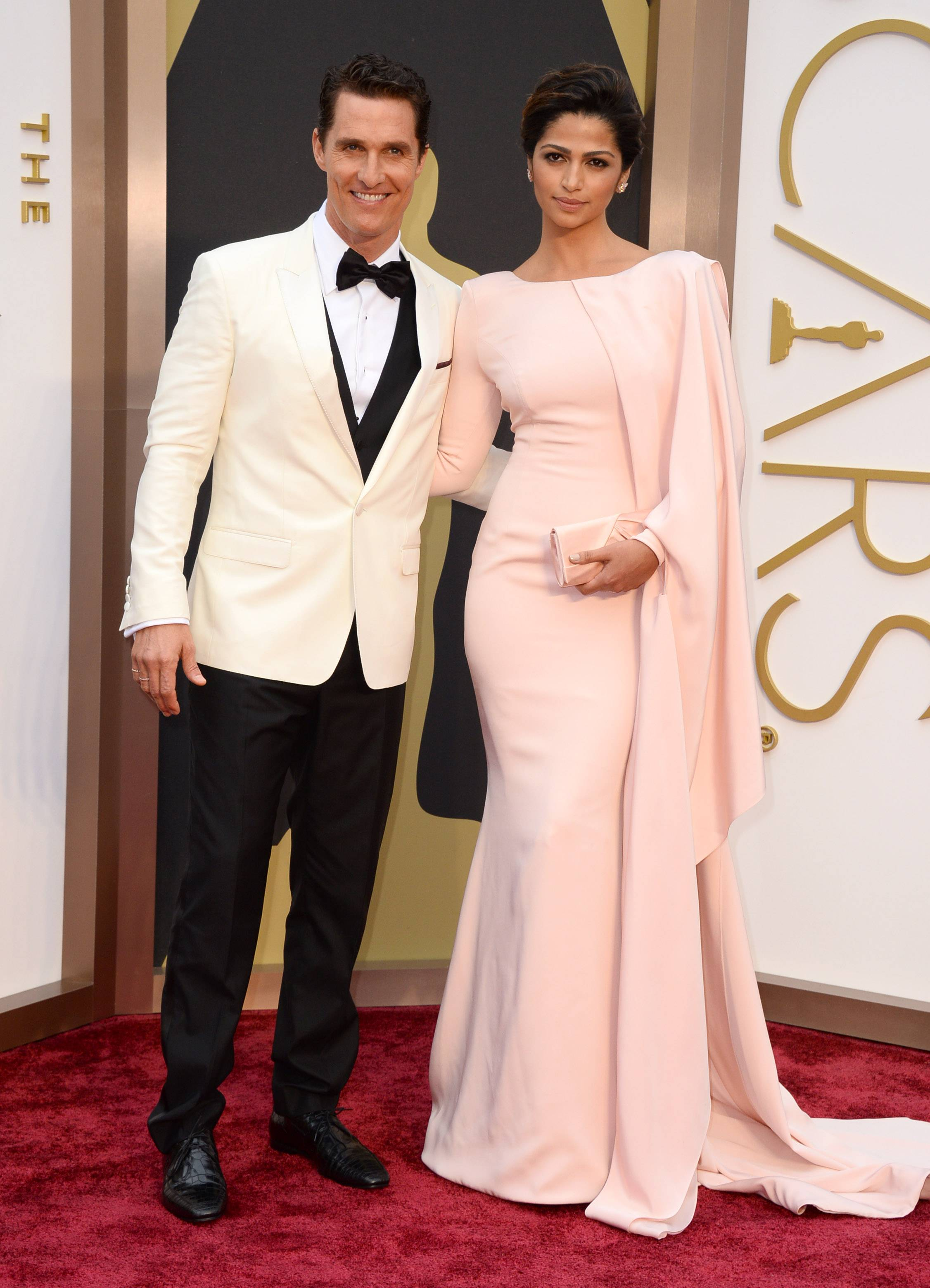 Best actor nominee Matthew McConaughey keeps wife Camila Alves close as they make their way into the Oscars ceremony.