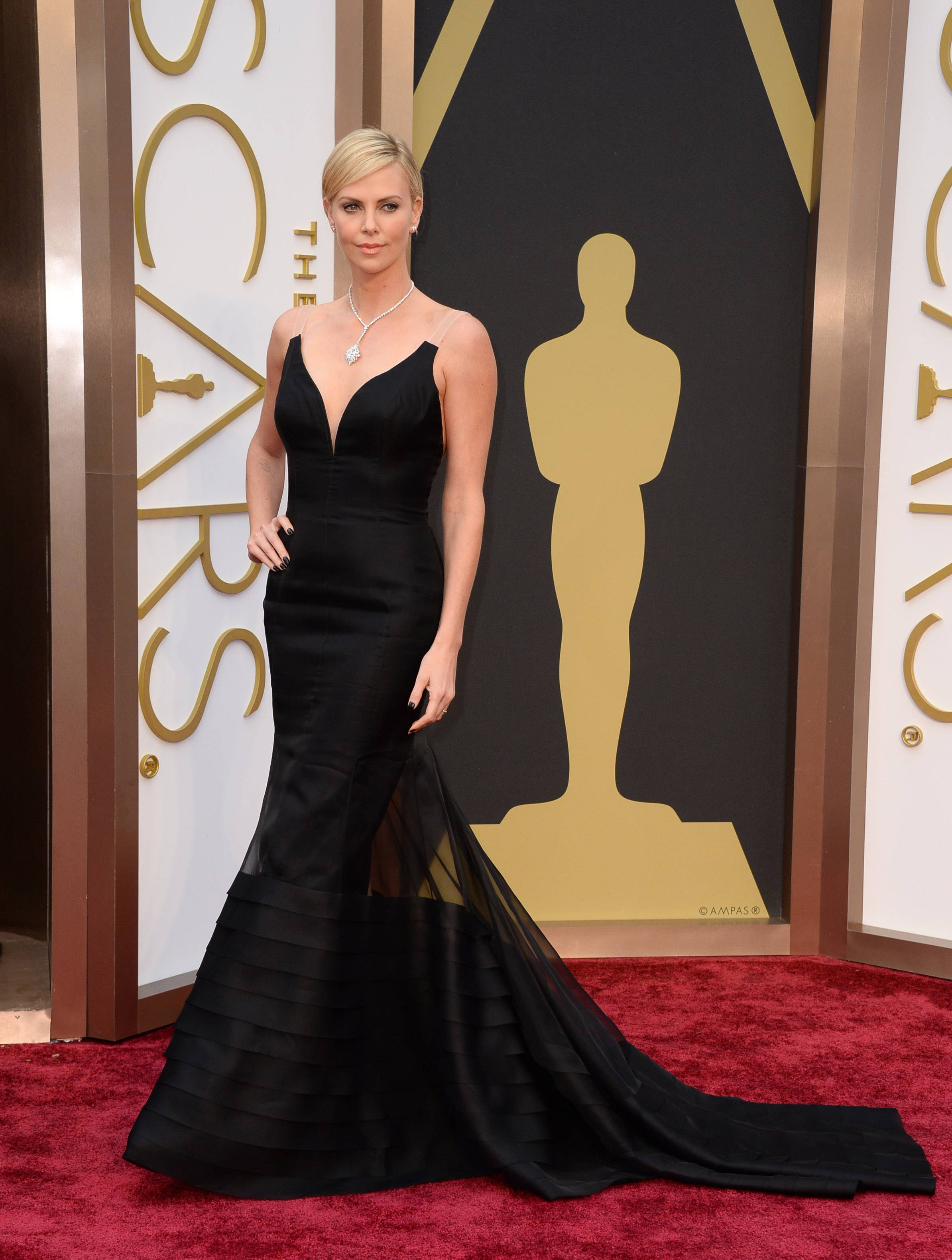 Oscar winner Charlize Theron puts some drama into her little black dress for Oscar night.