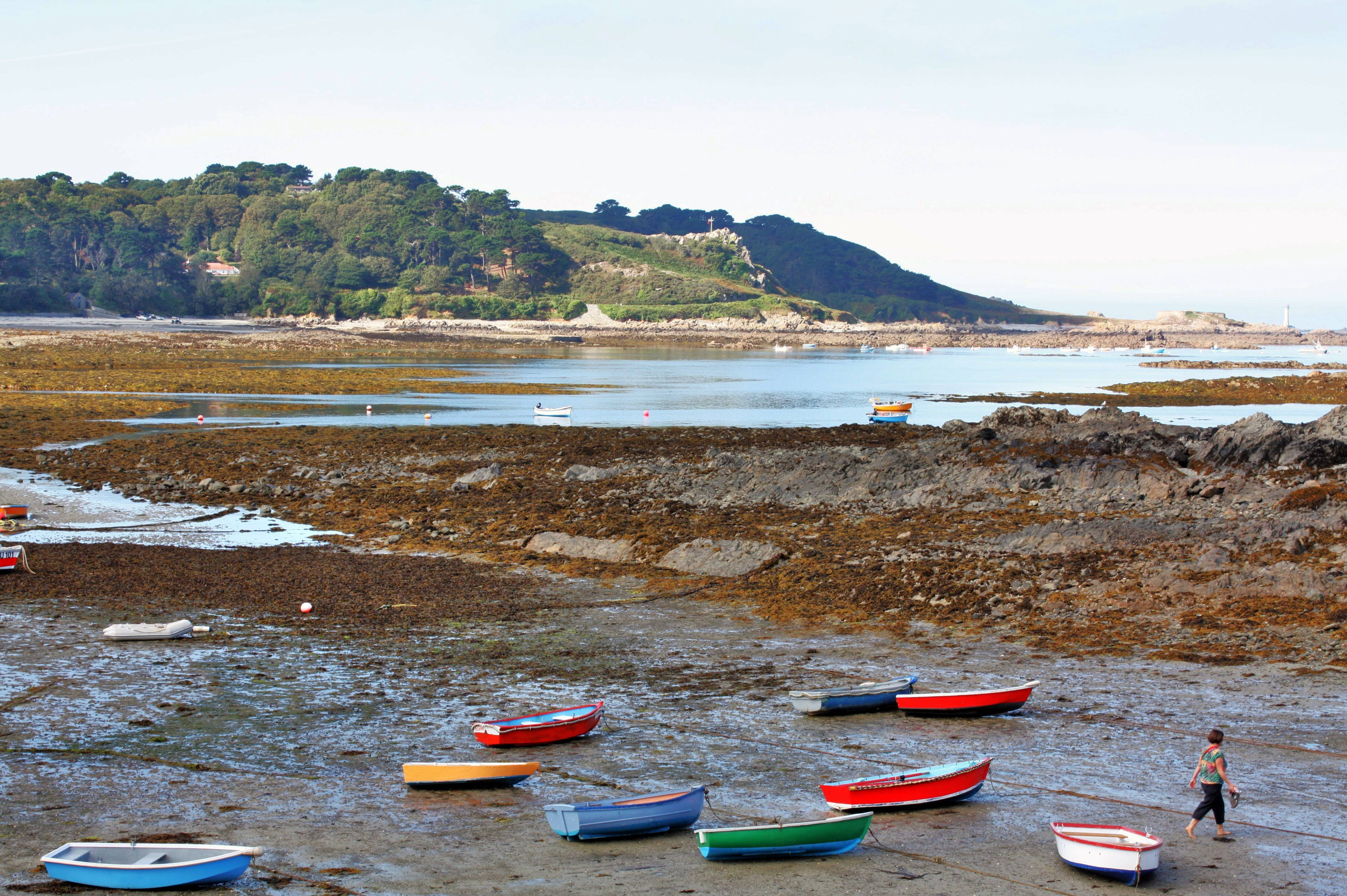 Brightly colored rowboats sit beached in Guernsey, one of the Channel Islands in the waters between England and France. The scene is one of many that can be enjoyed on a bike tour of the area offered while in port on a cruise.