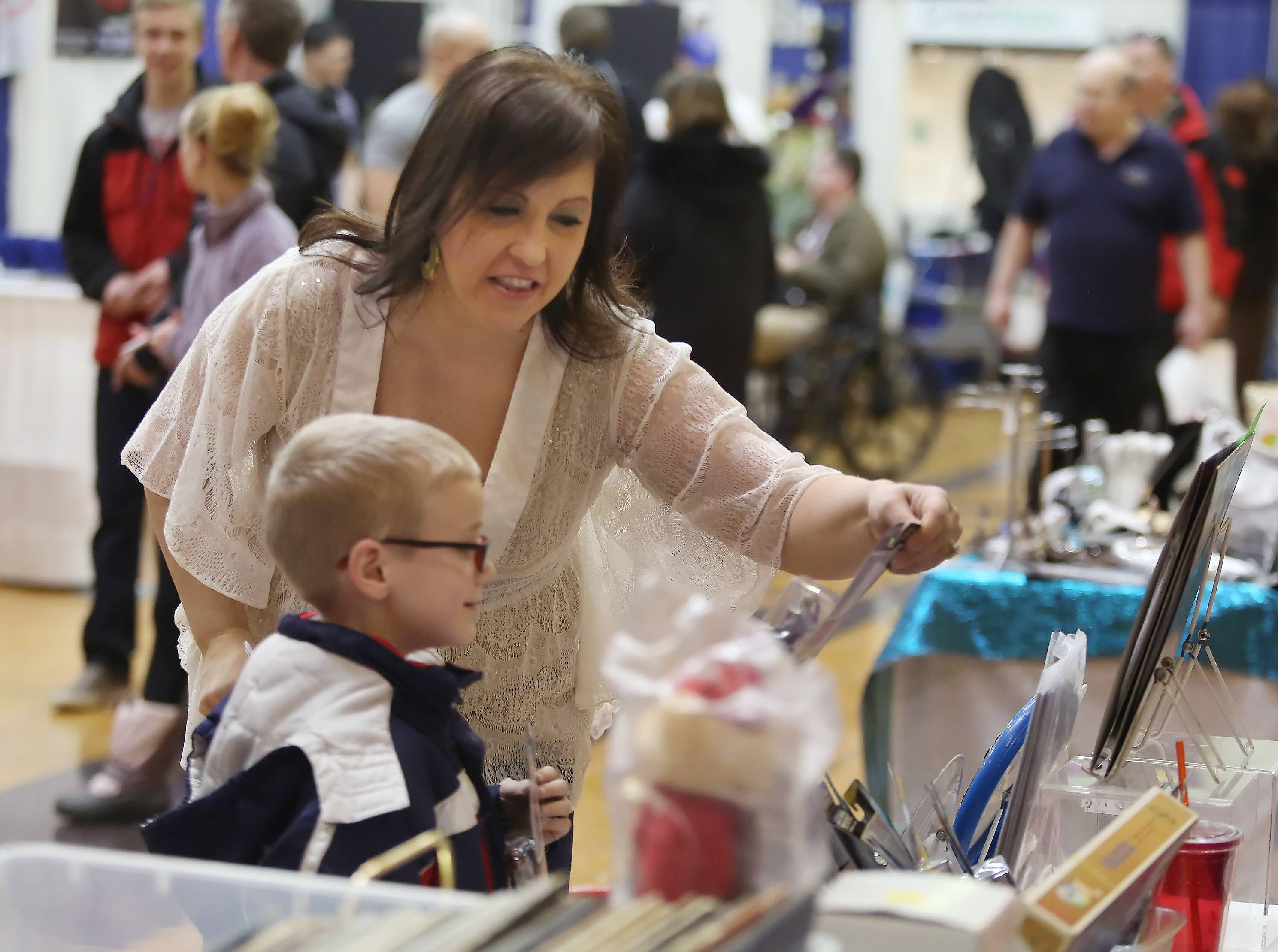 "Sheryl Ringel shows Jack Menzies, 6, of Wauconda a collectible toy at the Tri-County Pregnancy & Parenting Thrift Store booth during the ""Winter Blues Getaway"" Community Expo & Craft Show Sunday at Wauconda High School. The event featured over 70 exhibitors, craft show vendors and entertainment"