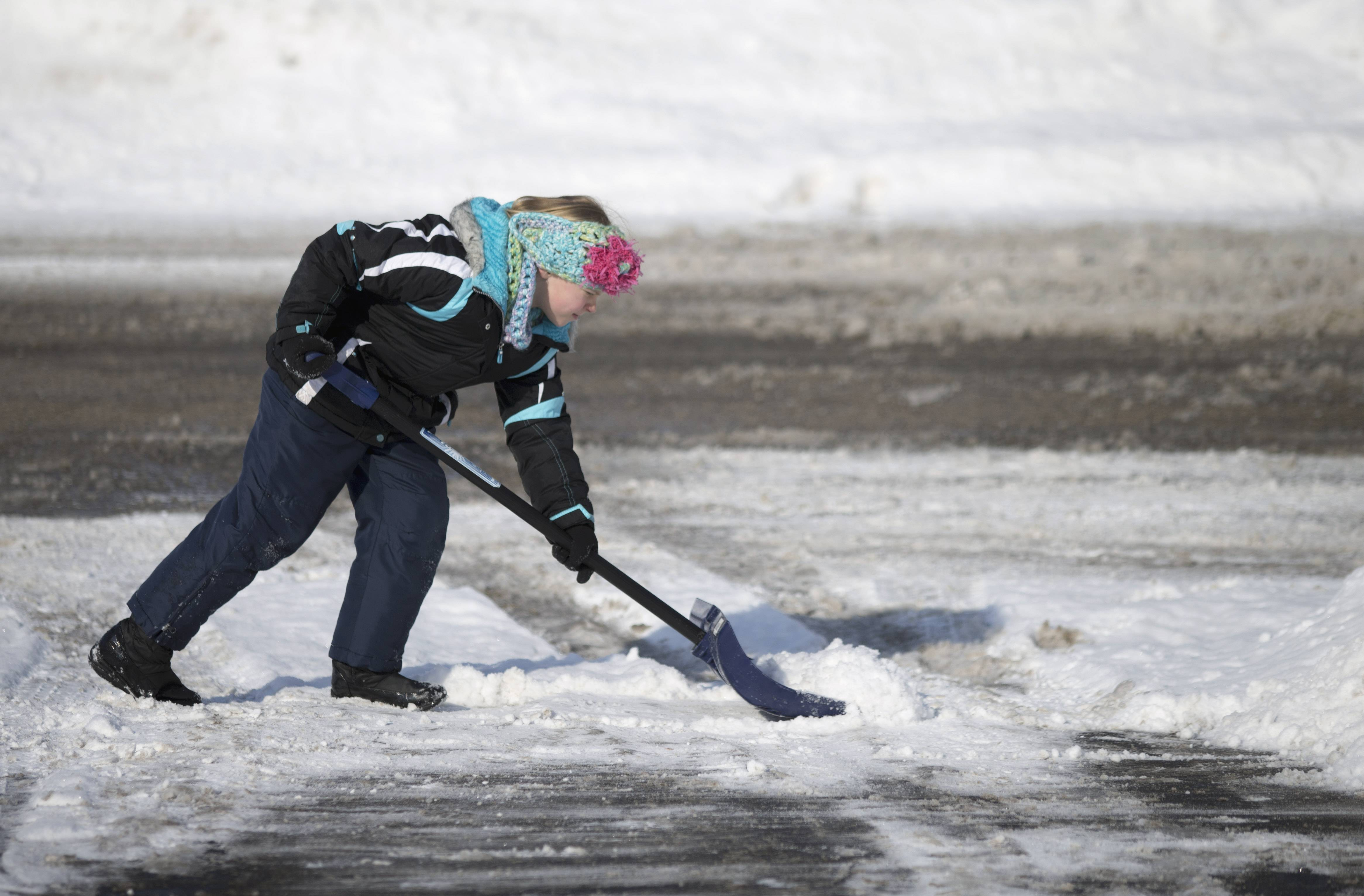 In this Feb. 9, 2014 photo, Katie Jensen, 9, shovels her family's driveway in Rockford, Ill, Jensen's third grade class at Brookview Elementary School has been helping clear snow from their neighbors' sidewalks and driveways.