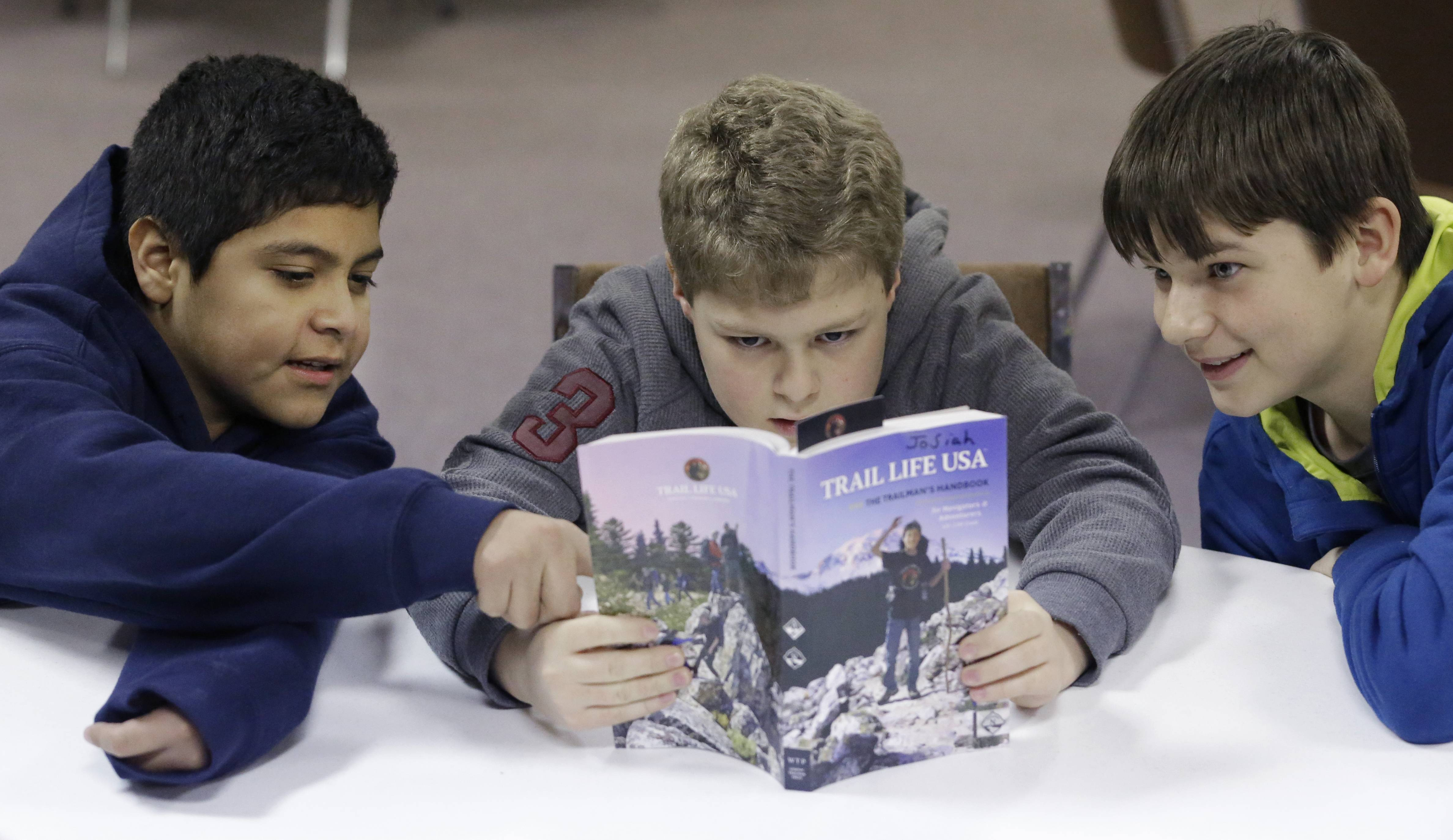 In this Tuesday, Feb. 4, 2014 photo, from left, Erick Izquierdo, Josiah Spear, 12, and Cole McSorley, 12, look at a Trail Life handbook during a gathering of members in North Richland Hills, Texas. Trail Life USA says it has established units in more than 40 states, mostly from Boy Scouts and parents who feel the century-old organization has lost its way.