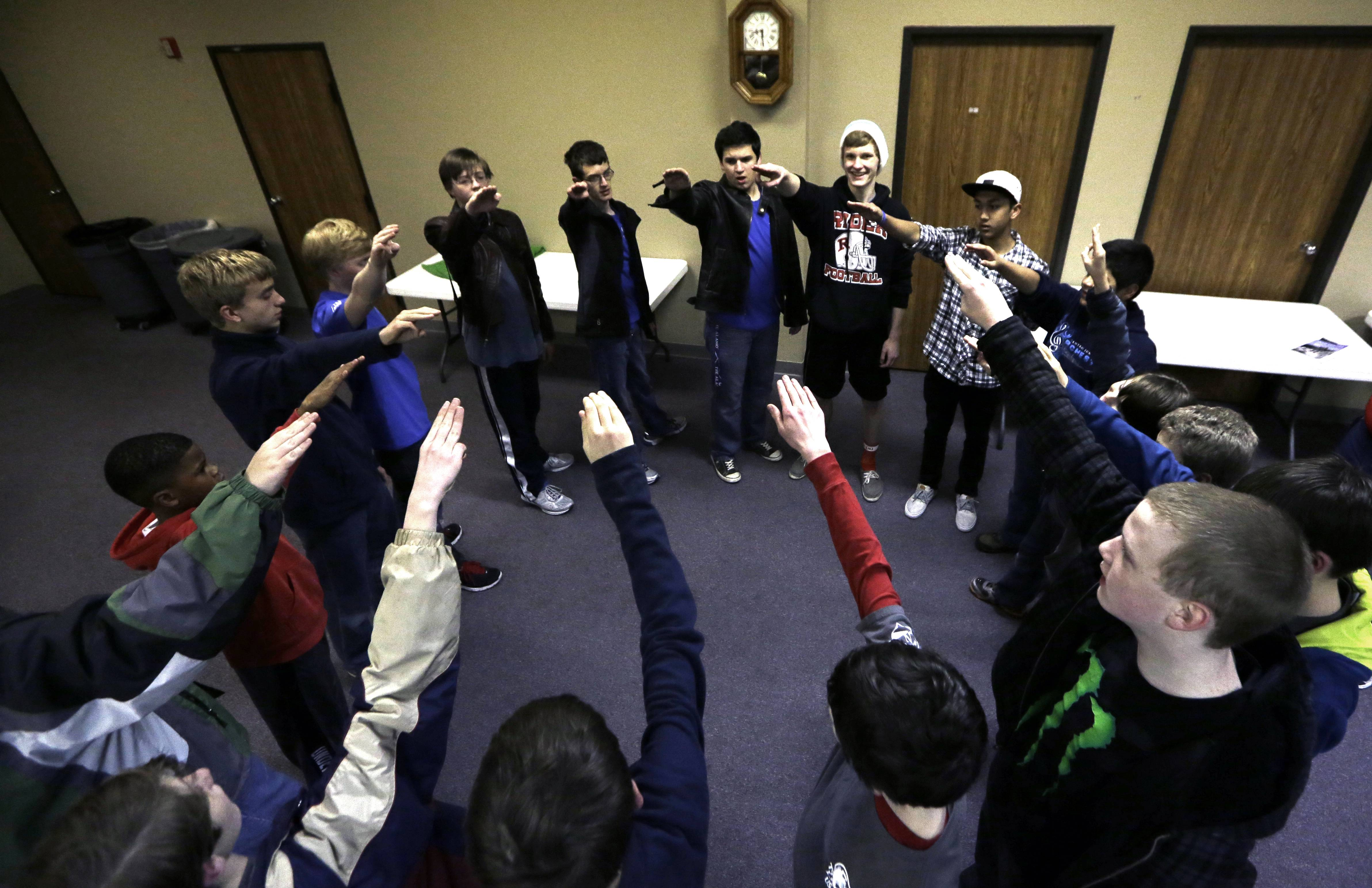 In this Tuesday, Feb. 4, 2014 photo, Trail Life members form a circle and recite the organization's creed during meeting in North Richland Hills, Texas. Trail Life USA, the new Christian-based alternative to the Boy Scouts of America, excludes openly gay members.