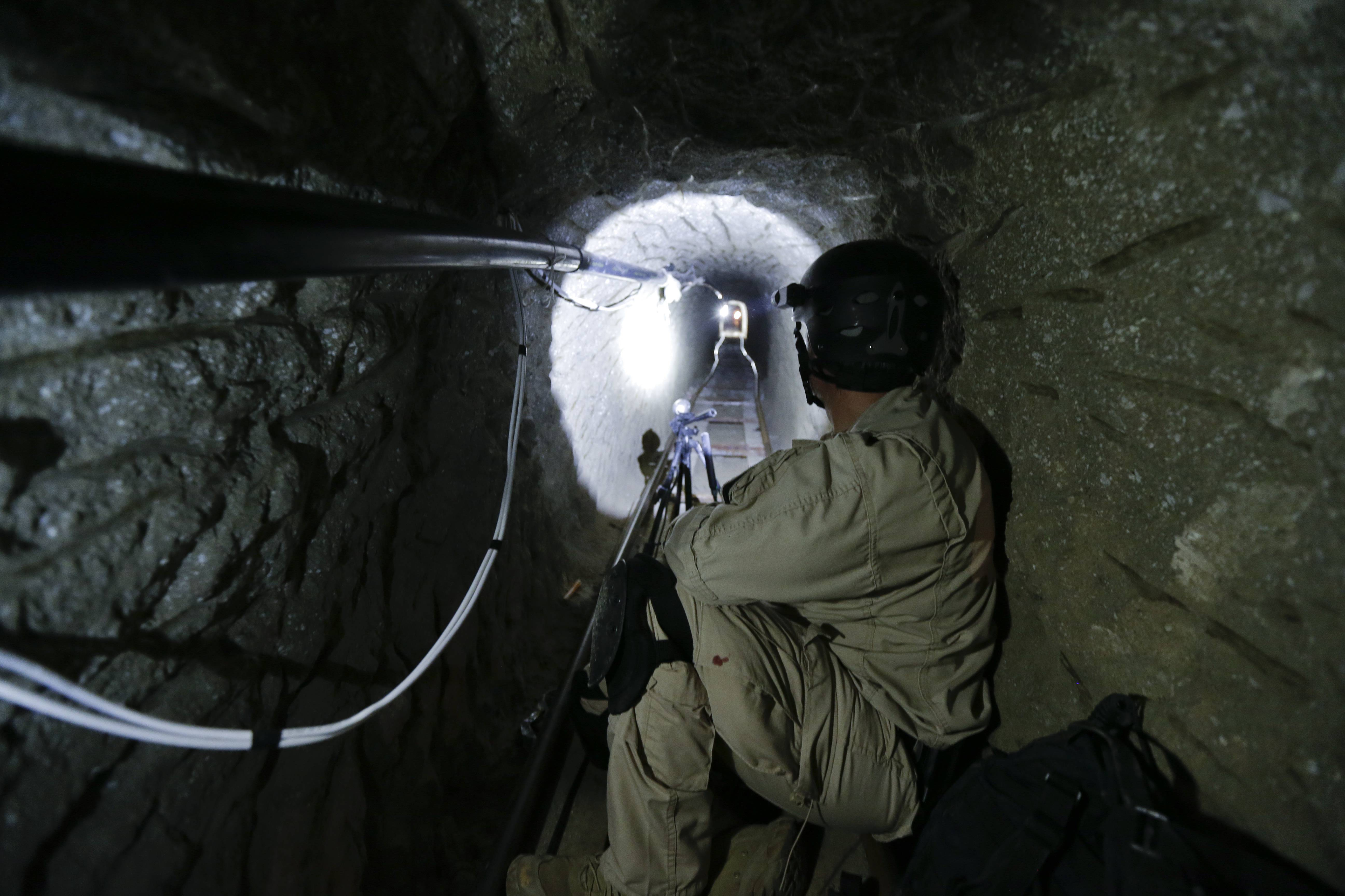 "In photo taken on Nov. 4, 2013, a Homeland Security Investigations member of the special response team looks south in a border tunnel equipped with lighting, ventilation and an electric rail system discovered between Tijuana, Mexico and San Diego in San Diego. Discovered on Oct. 30, 2013, the secret passage on the U.S.-Mexico border was linked by authorities to Mexico's Sinaloa cartel and its leader, Joaquin ""El Chapo"" Guzman, who was arrested on Feb. 22, 2014 in Maztalan, Mexico."