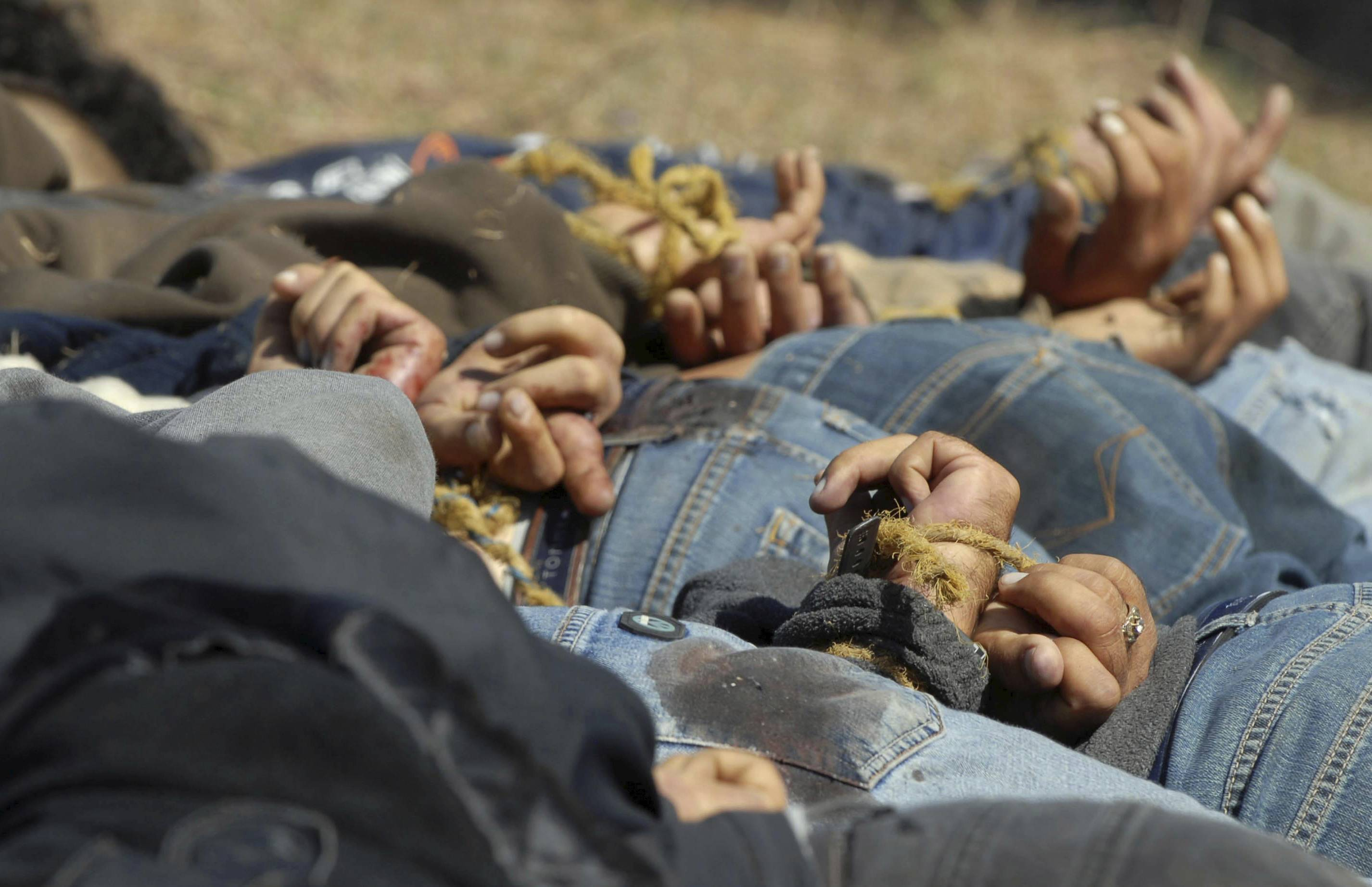 "In this Dec. 4, 2008, file photo, bodies from a total of 13 bullet-ridden men, with their hands tied behind their backs, victims of the drug war involving Joaquin ""El Chapo"" Guzman's Sinaloa cartel, lie in a field near the town of San Ignacio in the pacific state of Sinaloa, Mexico. Guzman and his cohorts waged an increasingly bloody war over the year with rival gangs."