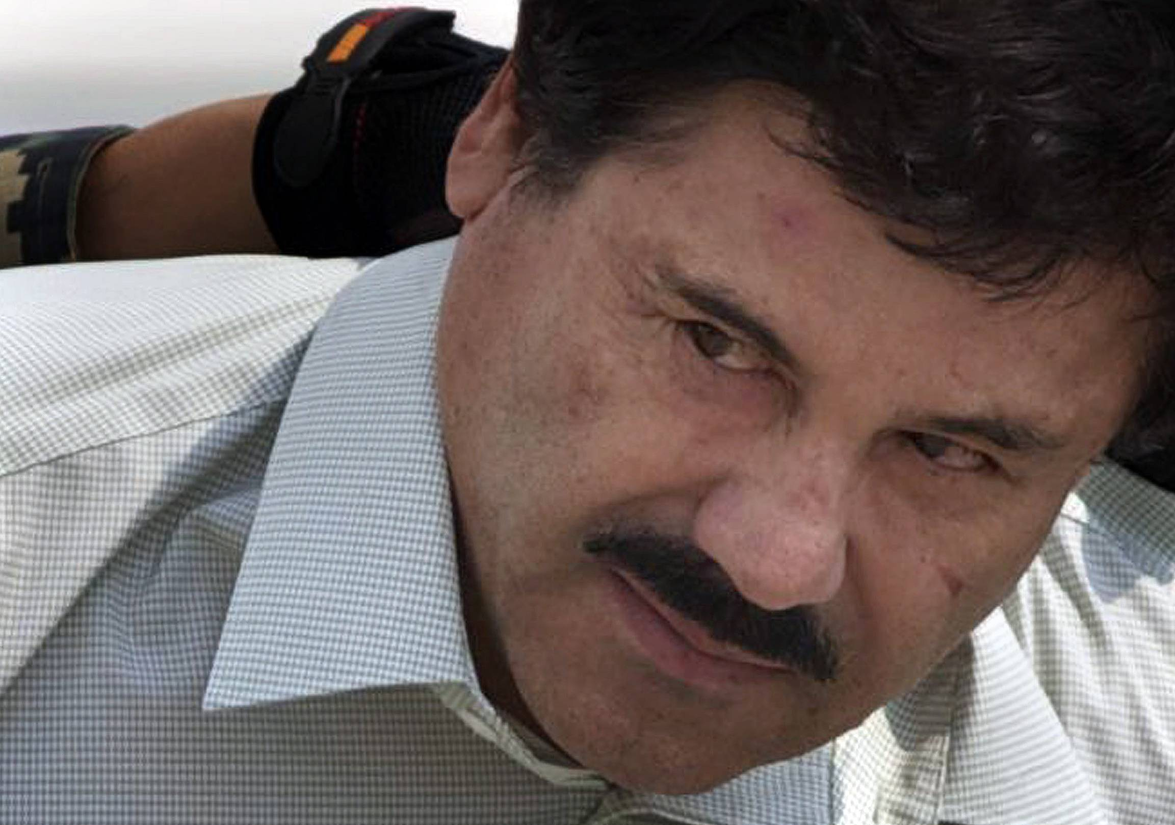 "In this Feb. 22, 2014, file photo, Joaquin ""El Chapo"" Guzman, in handcuffs, is escorted to a helicopter by Mexican navy marines in Mexico City, Mexico. At least seven U.S. courts have indictments pending against him, and several are pressing for extradition. In Mexico, he faces organized-crime charges in four Mexican states and in Mexico City. He could, barring another escape, spend the rest of his life behind bars."