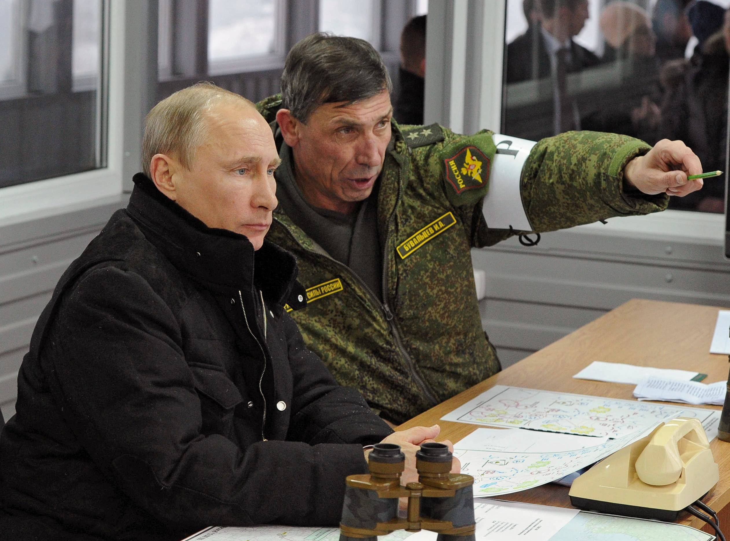 Russian President Vladimir Putin listens to Gen. Ivan Buvaltsev, right, as they observe a military exercise near St. Petersburg, Russia, Monday. Pro-Russian troops held all Ukrainian border posts Monday in Crimea, as well as all military facilities and a key ferry terminal, cementing their stranglehold on the strategic Ukrainian peninsula.