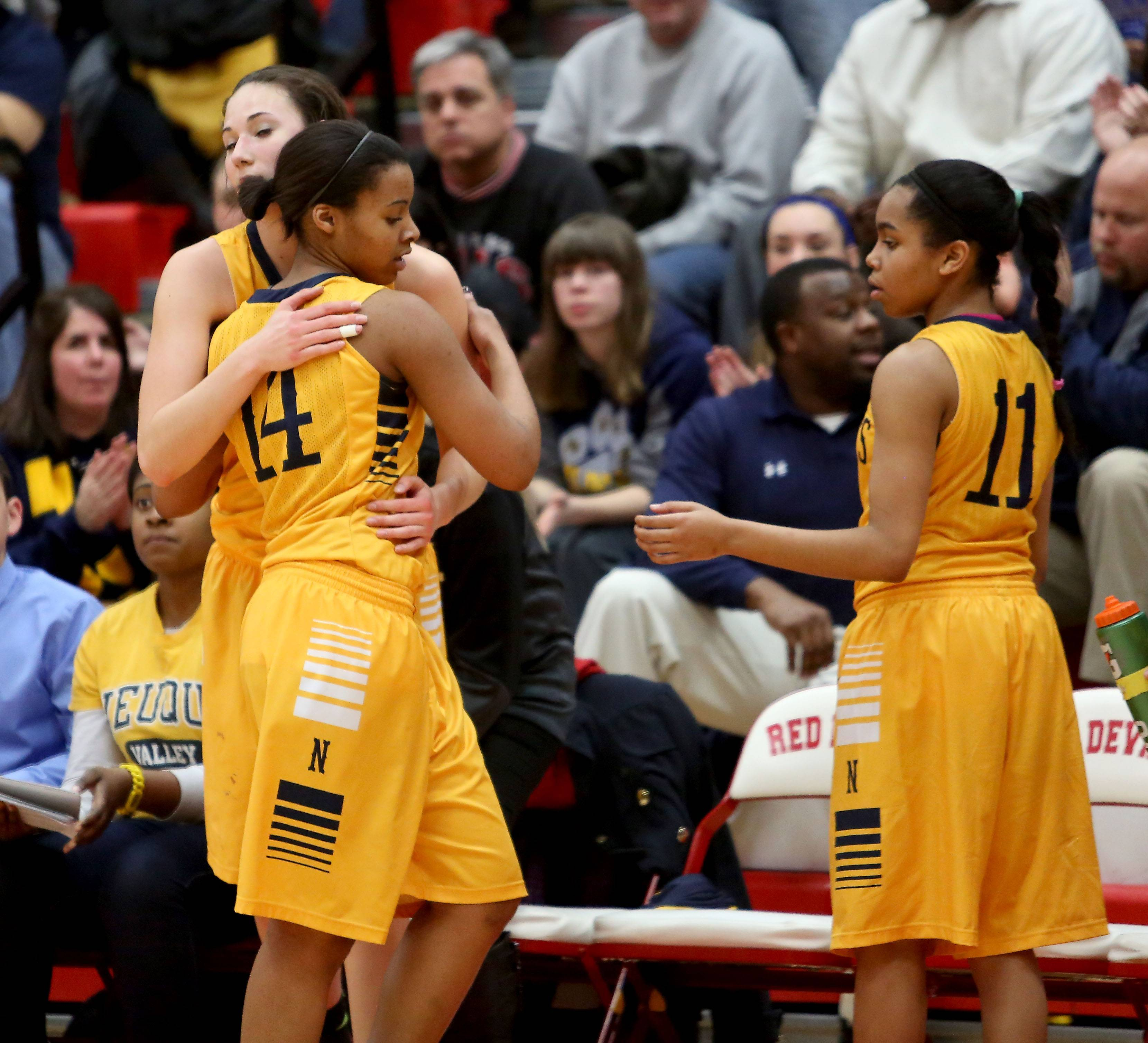 Neuqua Valley's Najee Smith, left, gets a hug from teammates as she comes off the floor during their loss to Whitney Young in Class 4A supersectional girls basketball at Hinsdale Central on Monday.