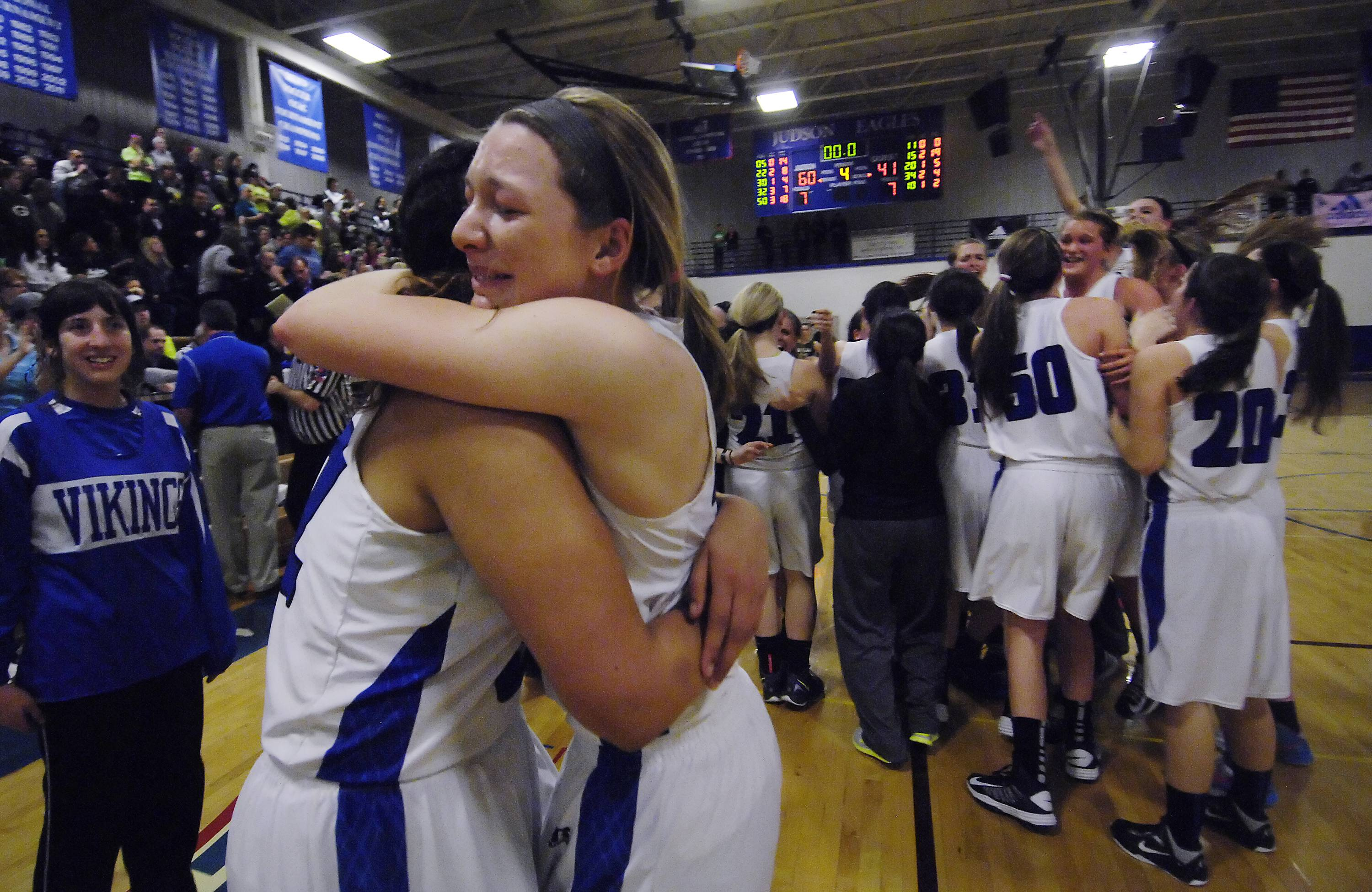 Geneva's Michaela Loebel is hugged by teammate Sidney Santos .